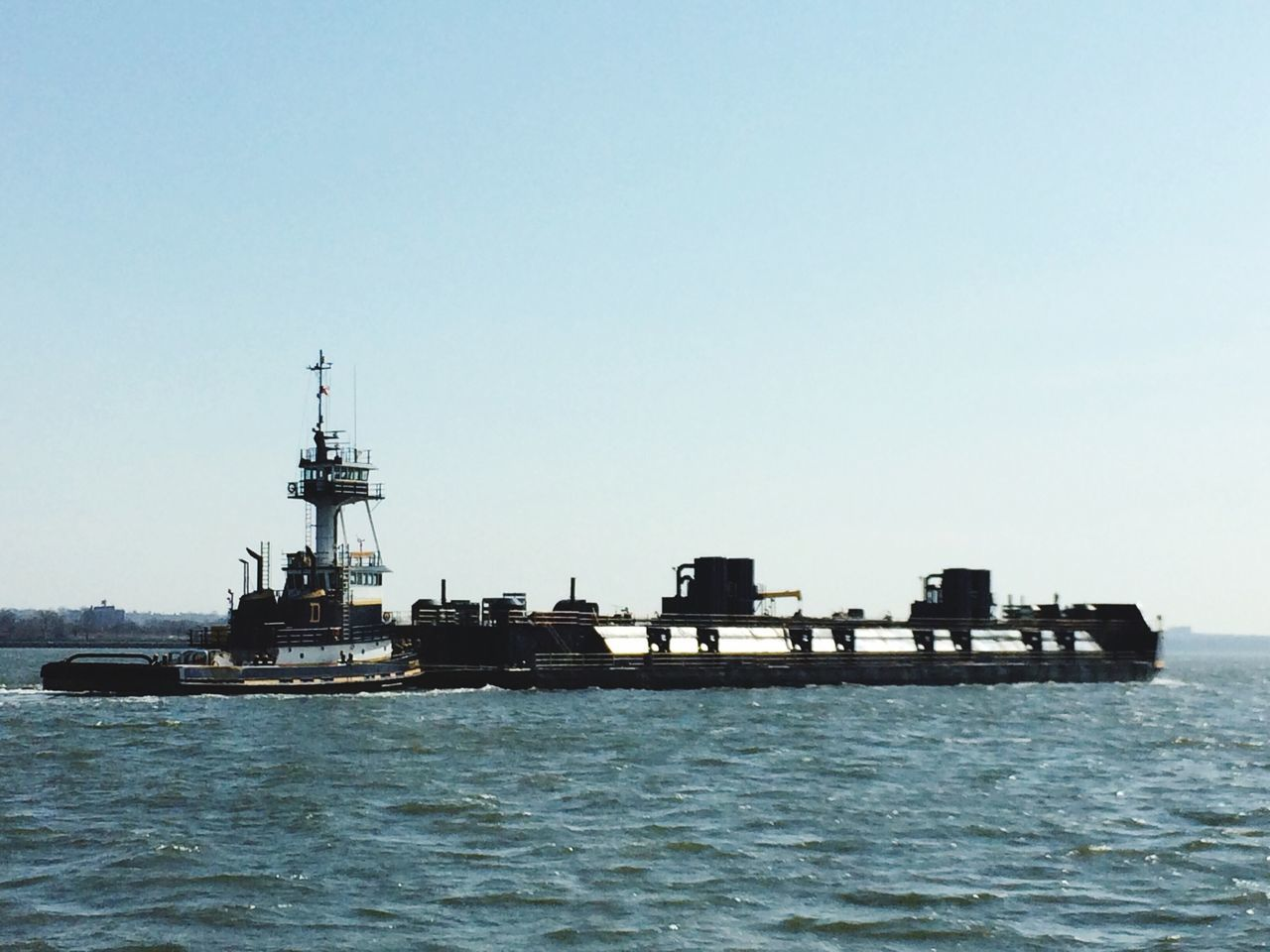 sea, water, nautical vessel, waterfront, copy space, clear sky, transportation, no people, day, outdoors, mode of transport, ship, nature, freight transportation, sailing, shipping, built structure, horizon over water, architecture, beauty in nature, lighthouse, offshore platform, sky, drilling rig