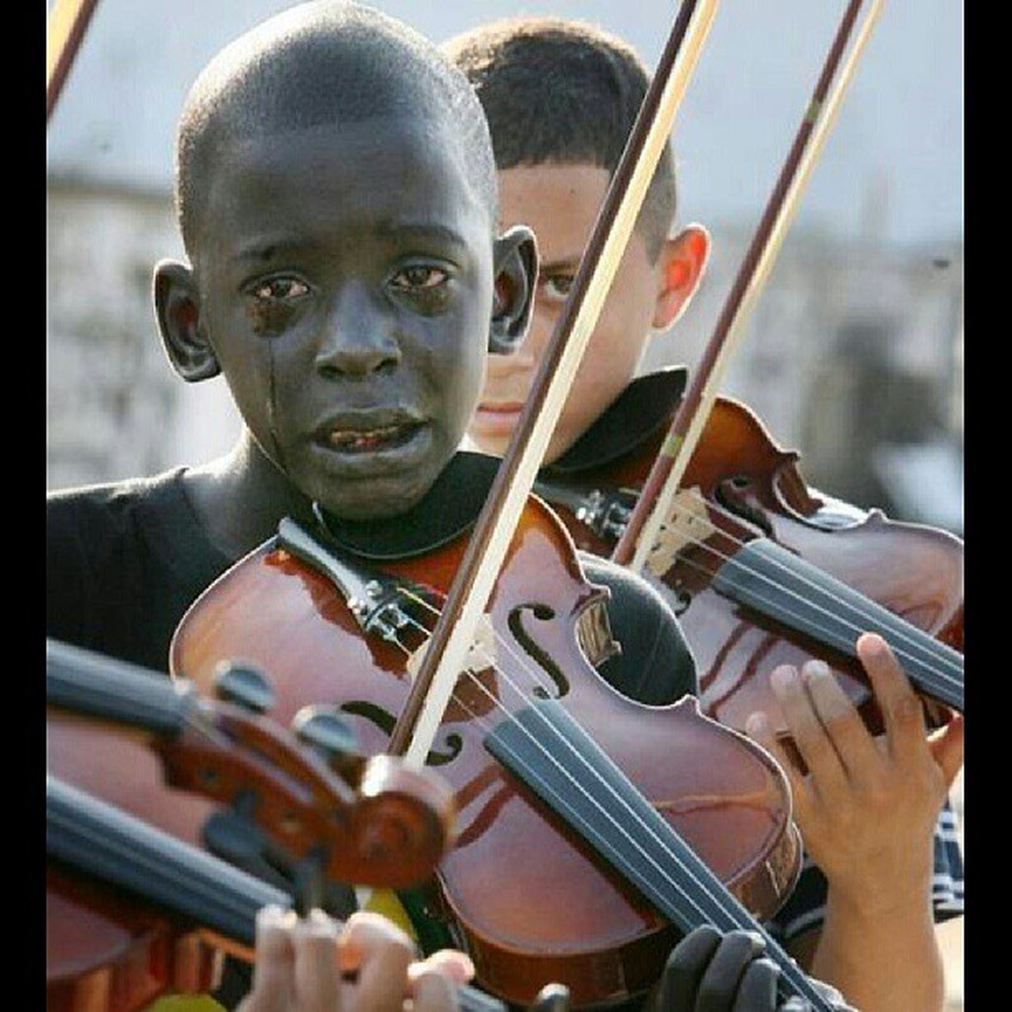 """"""" The boy who cries in the photo is Diego Frazao Torquato, who played the violin in the String Orchestra of the Afro Reggae. Afro Reggae is a non-profit organization that gives kids hope and an escape from their impoverished and crime ridden environments. The occasion was the funeral of his social project coordinator, Evandro João Silva, who was murdered in downtown Rio, Brazil. Diego contracted meningitis at age four, aggravated by pneumonia, and struggled with memory difficulties. He still managed to learn the violin. Diego, born and raised in the slums of Parada de Lucas, dreamed that the violin would take him to see the world. Sadly, shortly after this photo was taken Diego died of leukemia. At Diego's funeral José Júnior, the coordinator of Afro Reggae stated, 'I think the legacy of Diego is hope, it is the willingness to change, to transform'."""" DiegoFrazaoTorquato Restinpeace RestInParadise RIPDiegoFrazaoTorquato"""