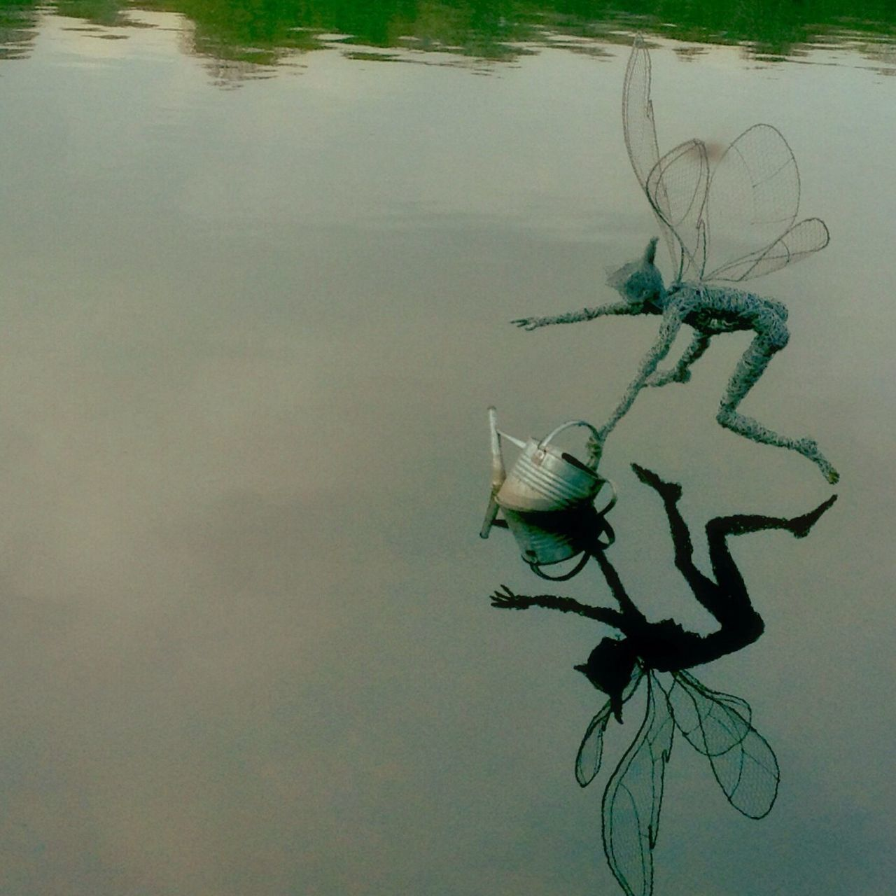 Reflection Of Sculpture On Water