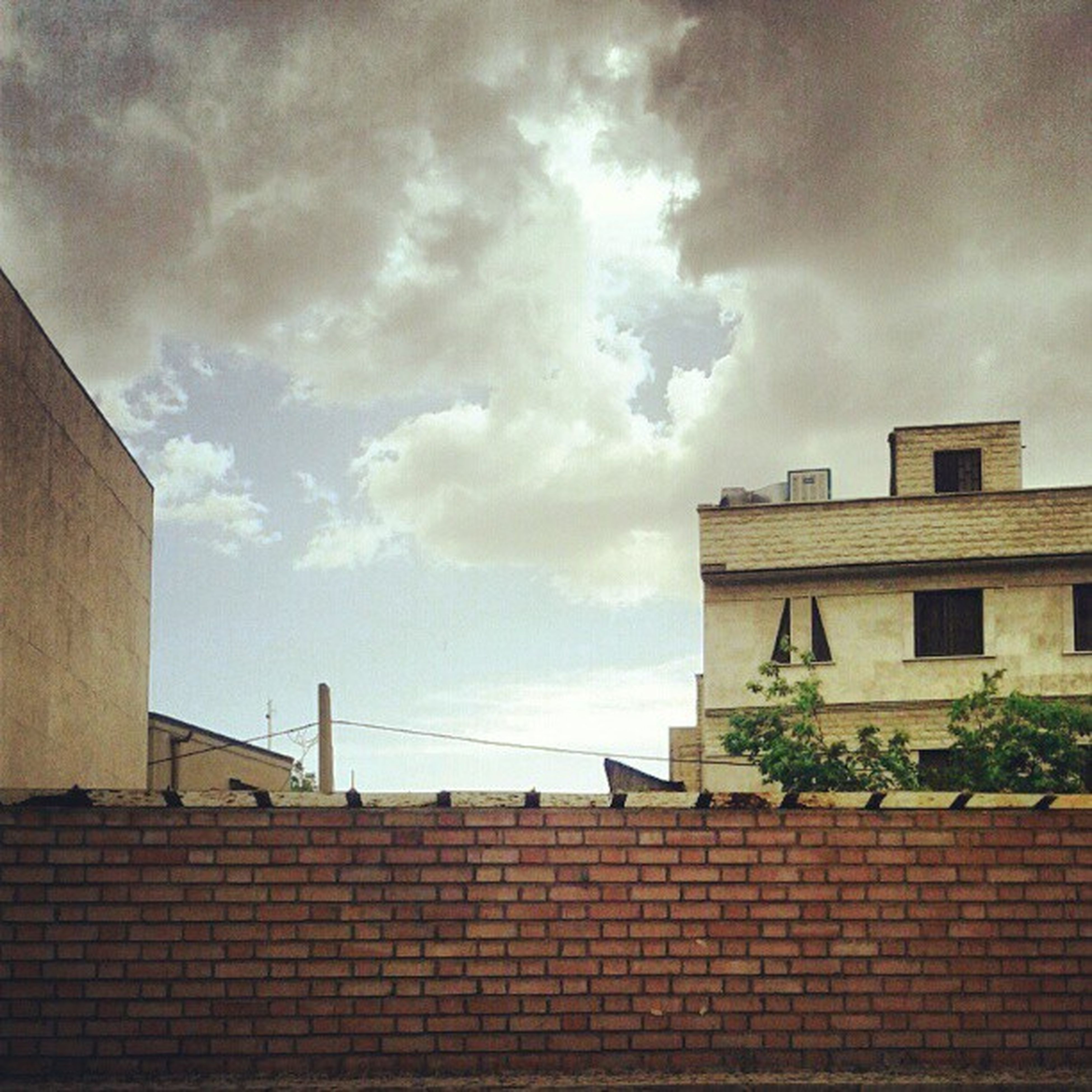 building exterior, architecture, built structure, sky, cloud - sky, cloudy, low angle view, cloud, brick wall, house, overcast, residential structure, weather, residential building, building, window, outdoors, day, wall - building feature, roof