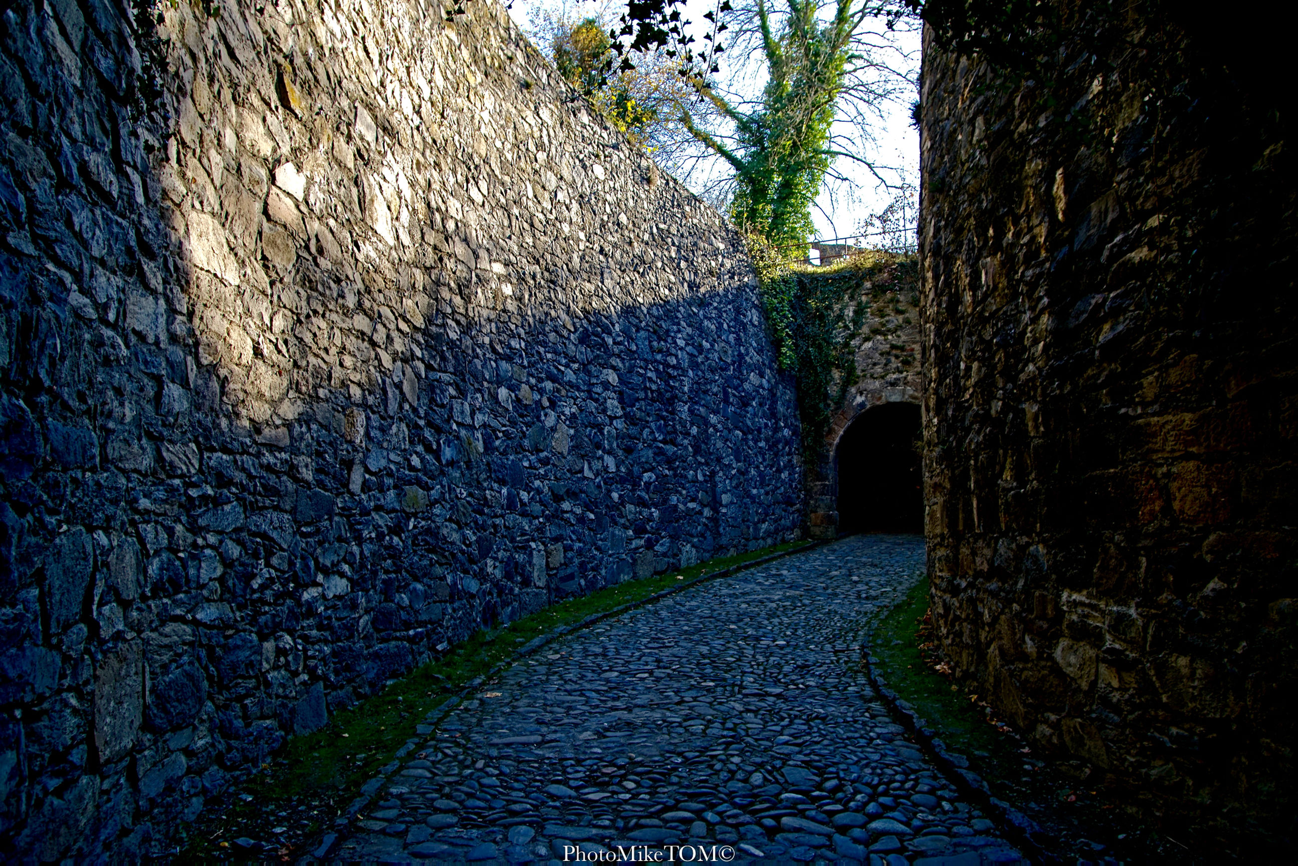 architecture, the way forward, built structure, arch, diminishing perspective, building exterior, stone wall, wall - building feature, cobblestone, walkway, wall, footpath, day, narrow, vanishing point, no people, brick wall, sunlight, stone material, textured
