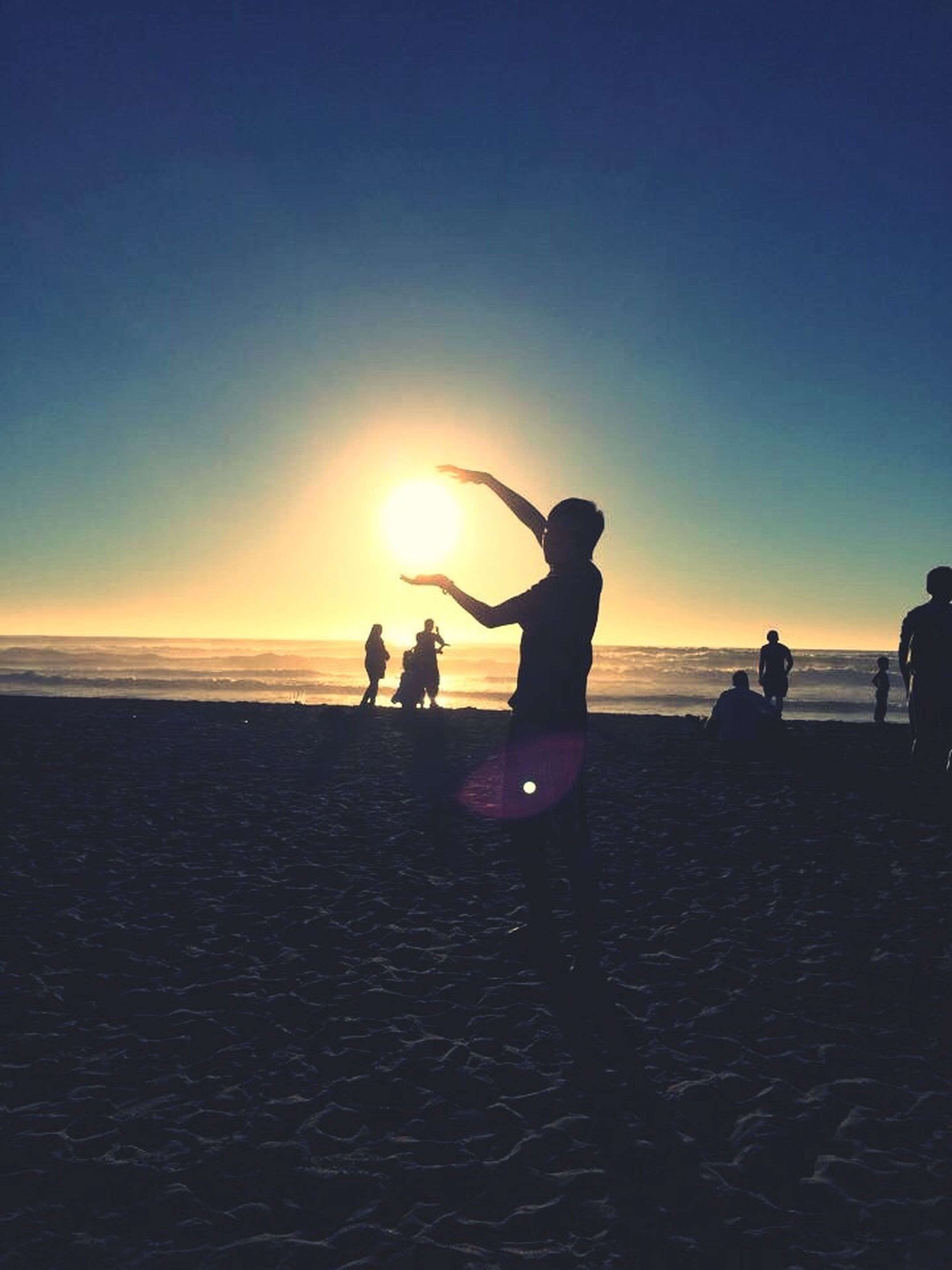 sunset, sea, horizon over water, beach, water, sun, silhouette, leisure activity, lifestyles, togetherness, orange color, men, shore, vacations, person, sky, scenics, beauty in nature, sunlight
