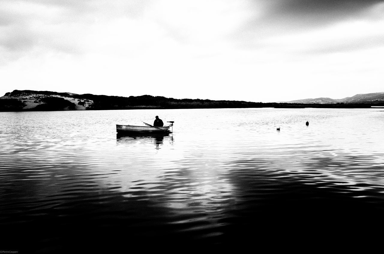 water, nautical vessel, waterfront, nature, real people, transportation, outdoors, sky, men, day, lake, scenics, cloud - sky, beauty in nature, tranquility, rowing, mountain, sailing, one person, oar, one man only, people