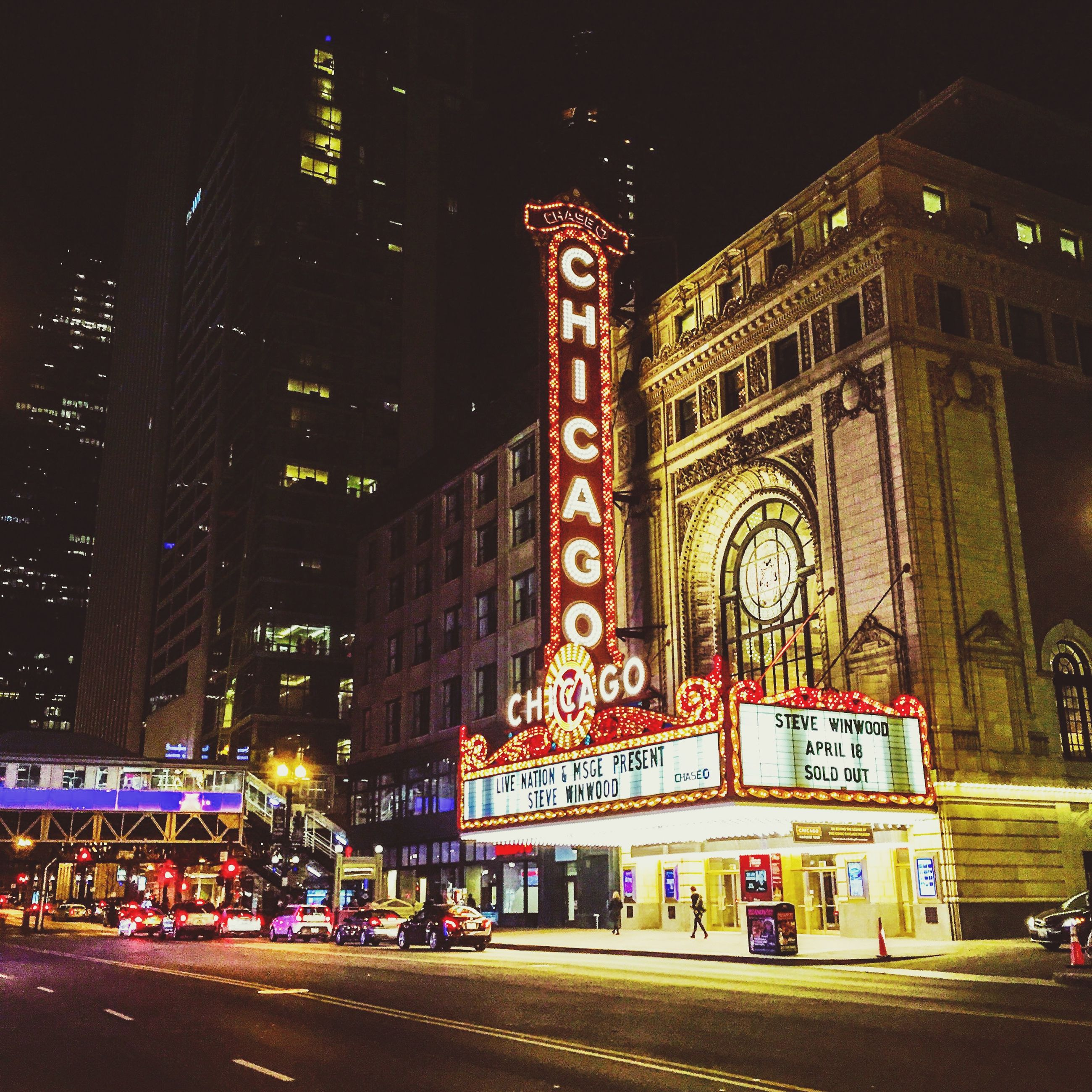 night, architecture, illuminated, building exterior, built structure, city, street, city life, large group of people, text, travel destinations, person, road, men, outdoors, capital cities, travel, western script, city street