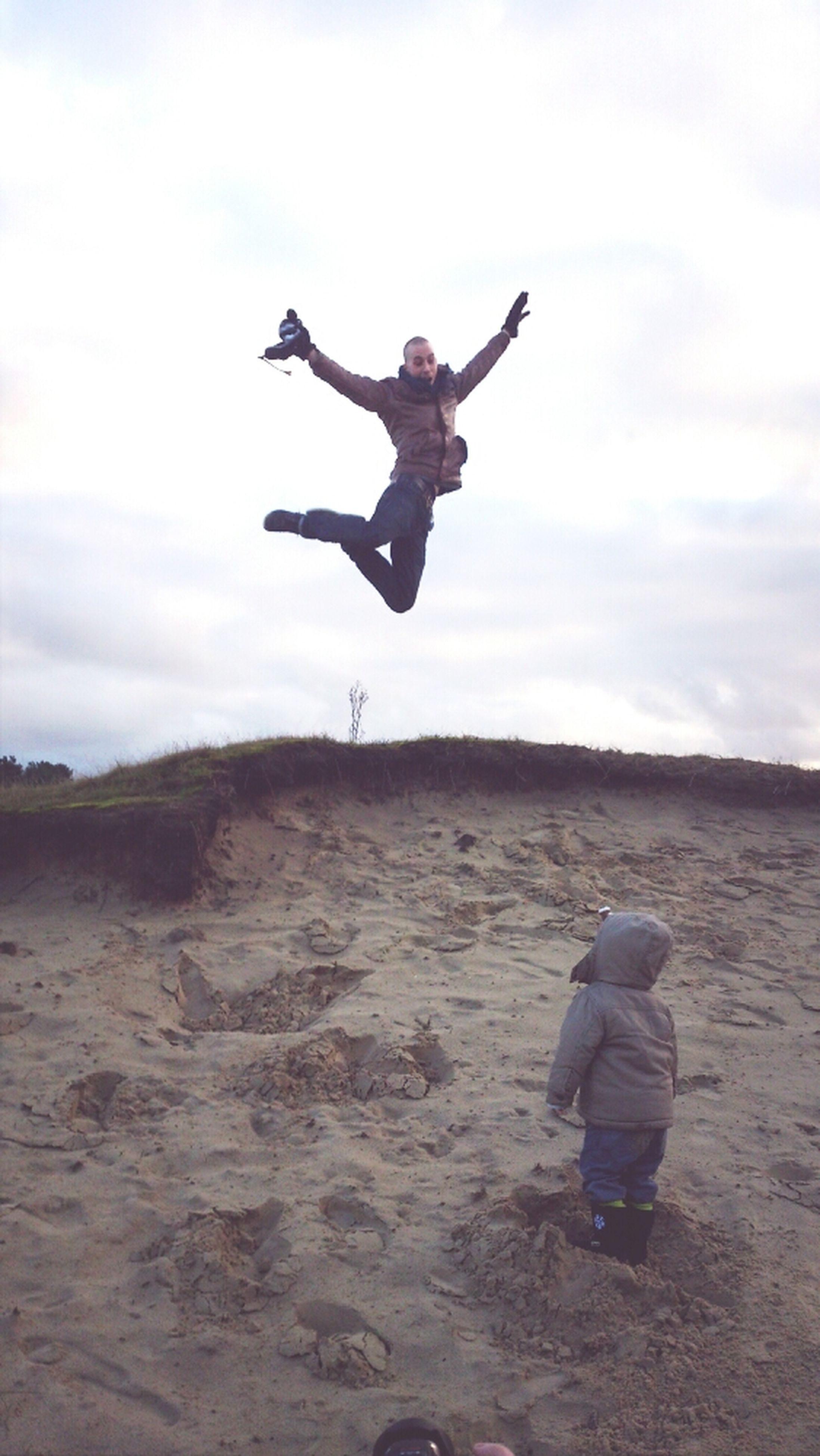full length, leisure activity, lifestyles, mid-air, sky, arms outstretched, jumping, casual clothing, cloud - sky, childhood, fun, enjoyment, carefree, freedom, men, person, low angle view, vitality