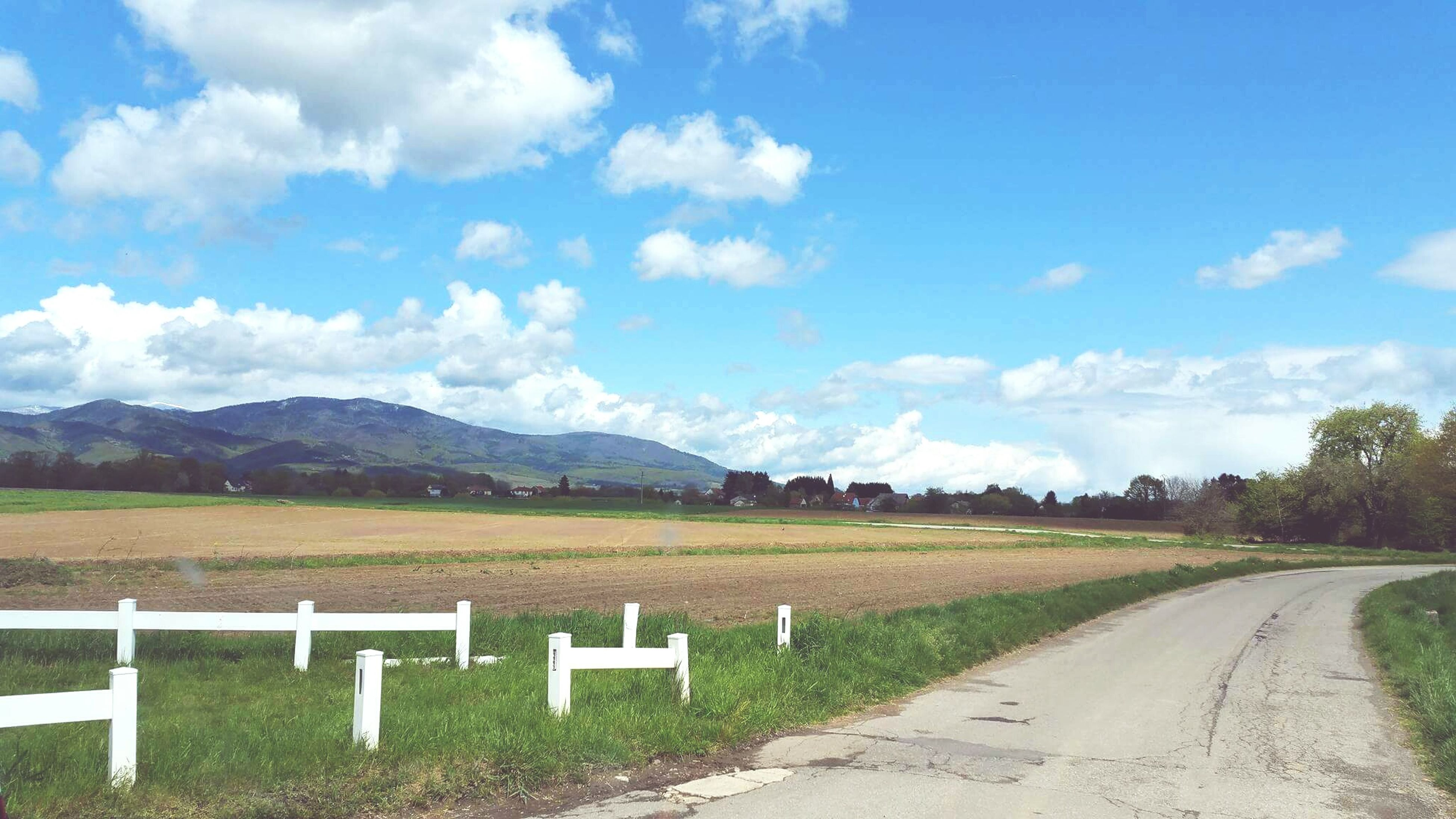 sky, road, the way forward, transportation, cloud - sky, landscape, road marking, country road, empty, cloud, tranquility, tranquil scene, blue, grass, diminishing perspective, field, scenics, mountain, nature, vanishing point