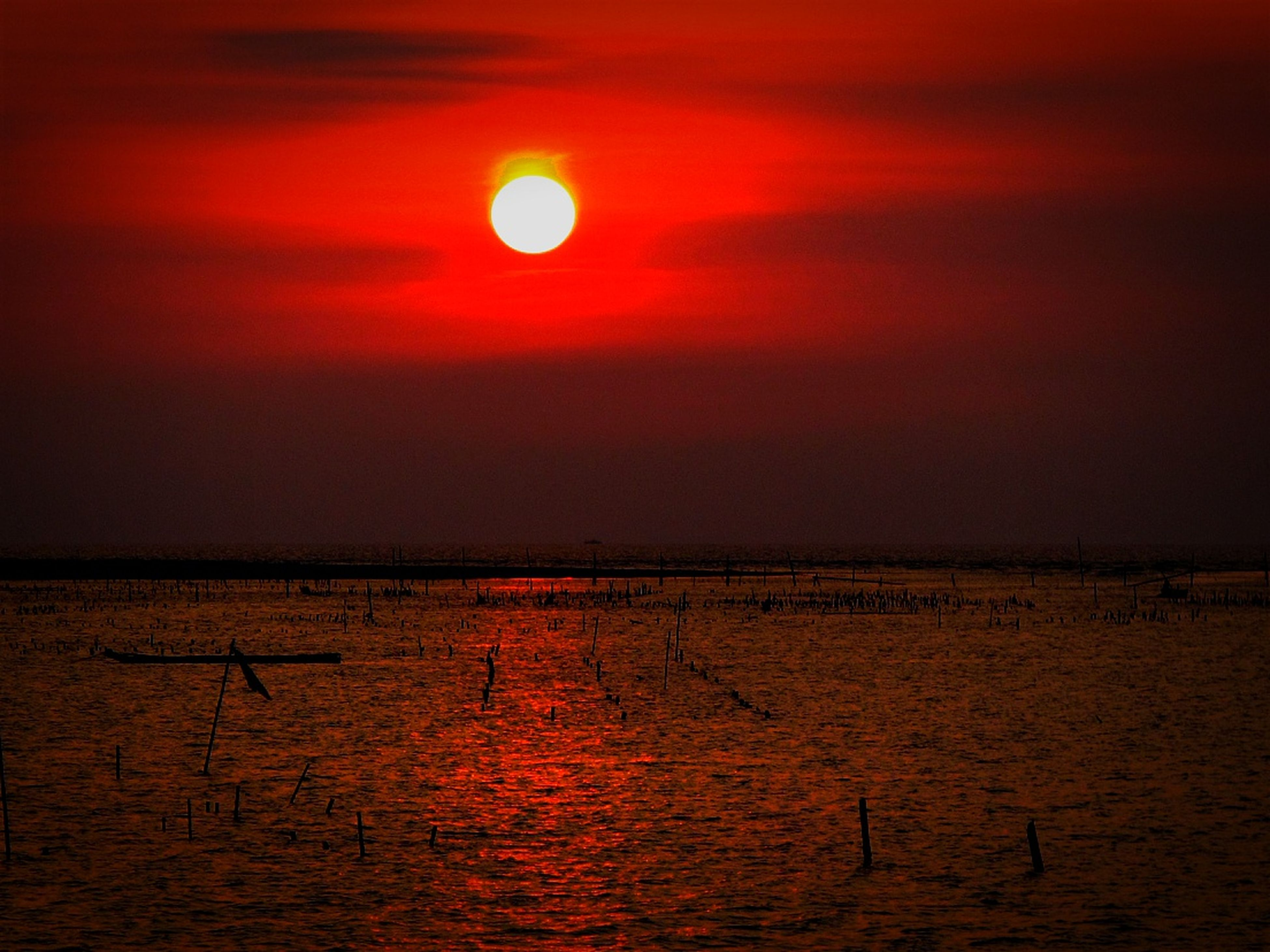 sunset, sun, orange color, water, scenics, tranquil scene, tranquility, sea, beauty in nature, idyllic, nature, sky, horizon over water, reflection, silhouette, waterfront, remote, outdoors, non-urban scene, no people