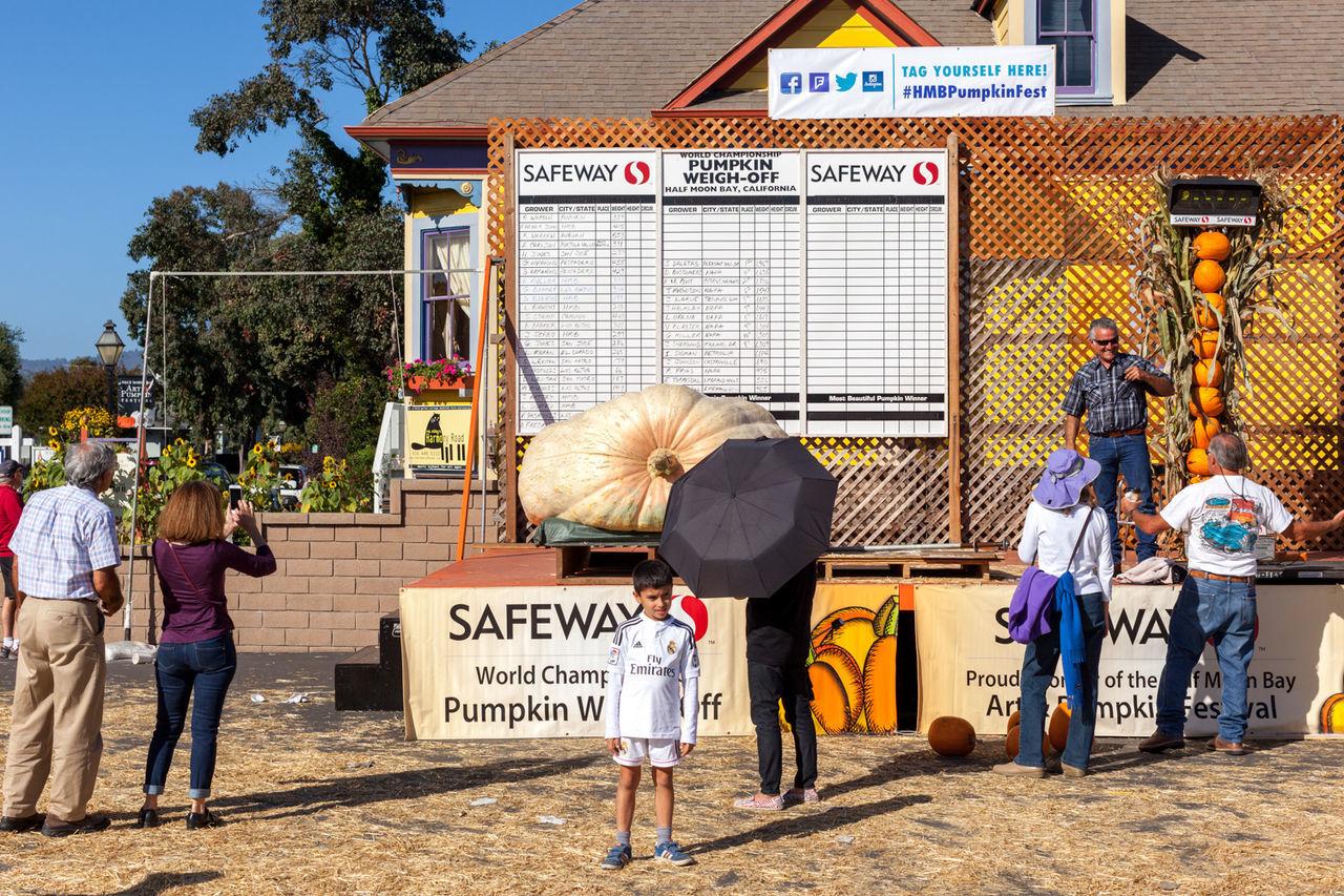 Spectators inspect the 2015 heaviest pumpkin winner of the half moon bay pumpkin festival. Boy Giant Pumpkin Half Moon Bay, California Information Sign Outdoors Pumpkin Contest Weigh Ins Weigh Off Winner
