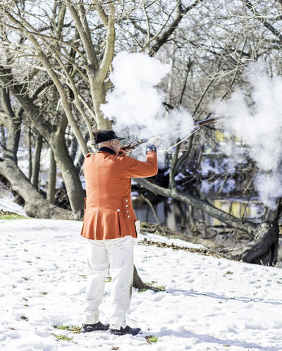 Bare Tree Branch Casual Clothing Cold Temperature Covering Day Full Length Leisure Activity Lifestyles Outdoors Real People Rear View Rifle Falls State Park Season  Snow Standing Tree Warm Clothing Weapon Weather Winter
