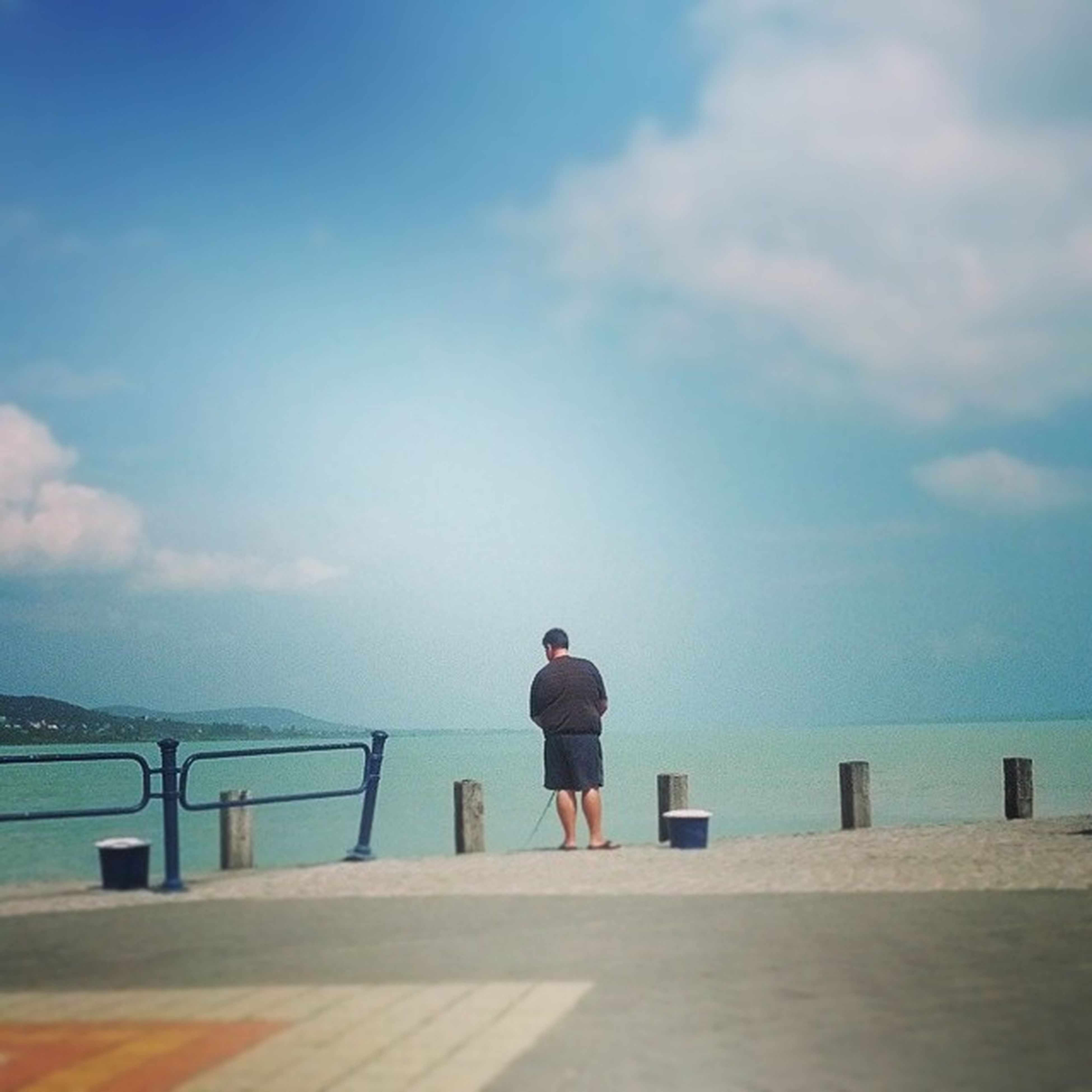 rear view, sky, water, railing, full length, standing, sea, cloud - sky, pier, lifestyles, leisure activity, tranquility, tranquil scene, looking at view, men, scenics, cloud, blue