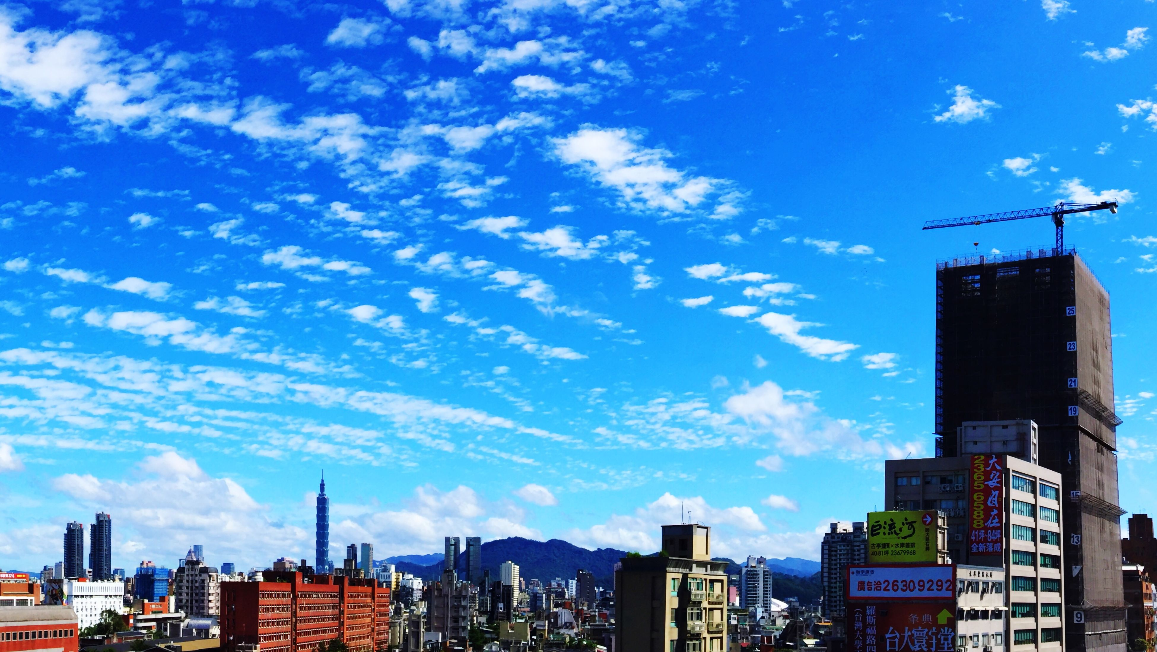 building exterior, architecture, built structure, sky, city, cloud - sky, blue, low angle view, residential building, building, cloud, cityscape, tower, residential structure, skyscraper, tall - high, residential district, city life, sunlight, day