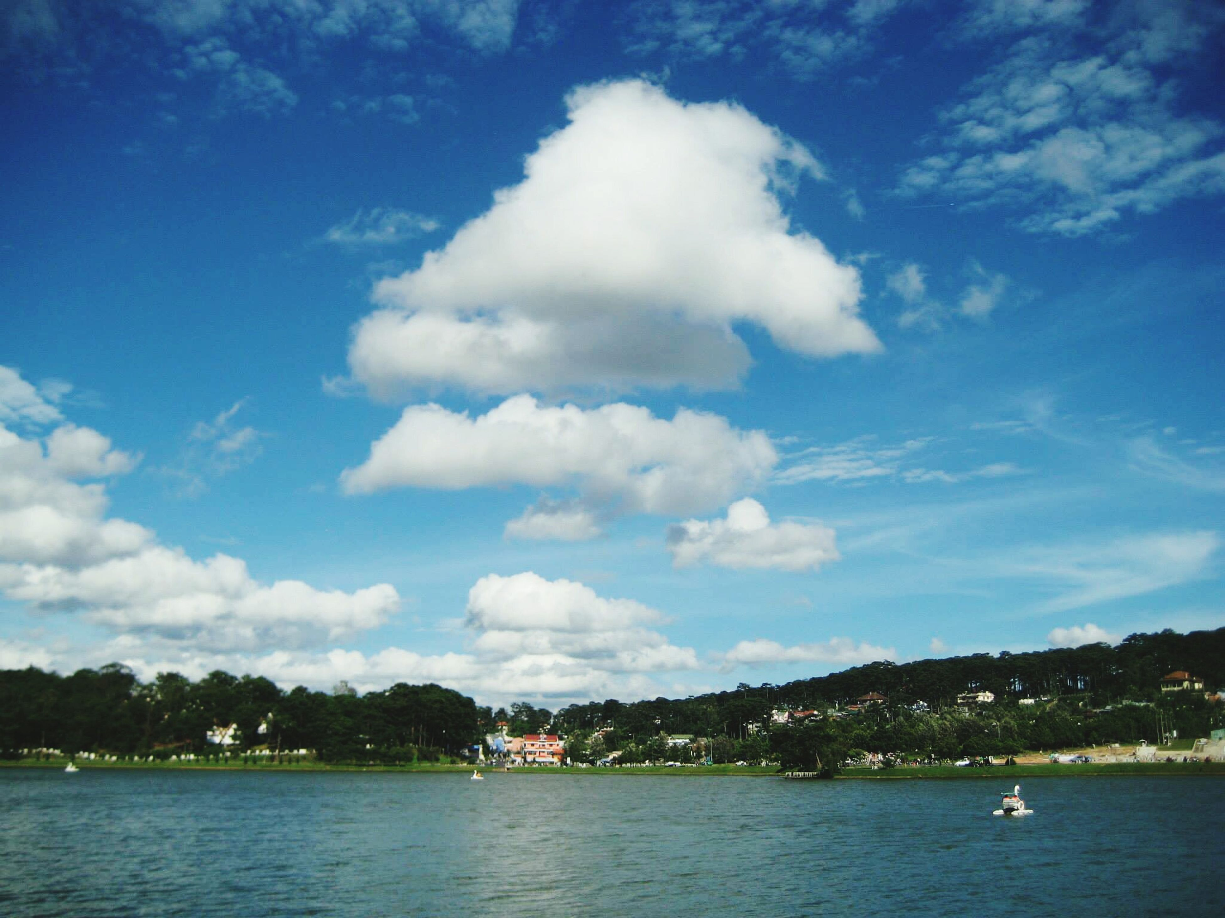 water, waterfront, nautical vessel, sky, boat, transportation, tree, cloud - sky, mode of transport, sea, tranquil scene, tranquility, blue, scenics, river, cloud, lake, nature, beauty in nature, mountain
