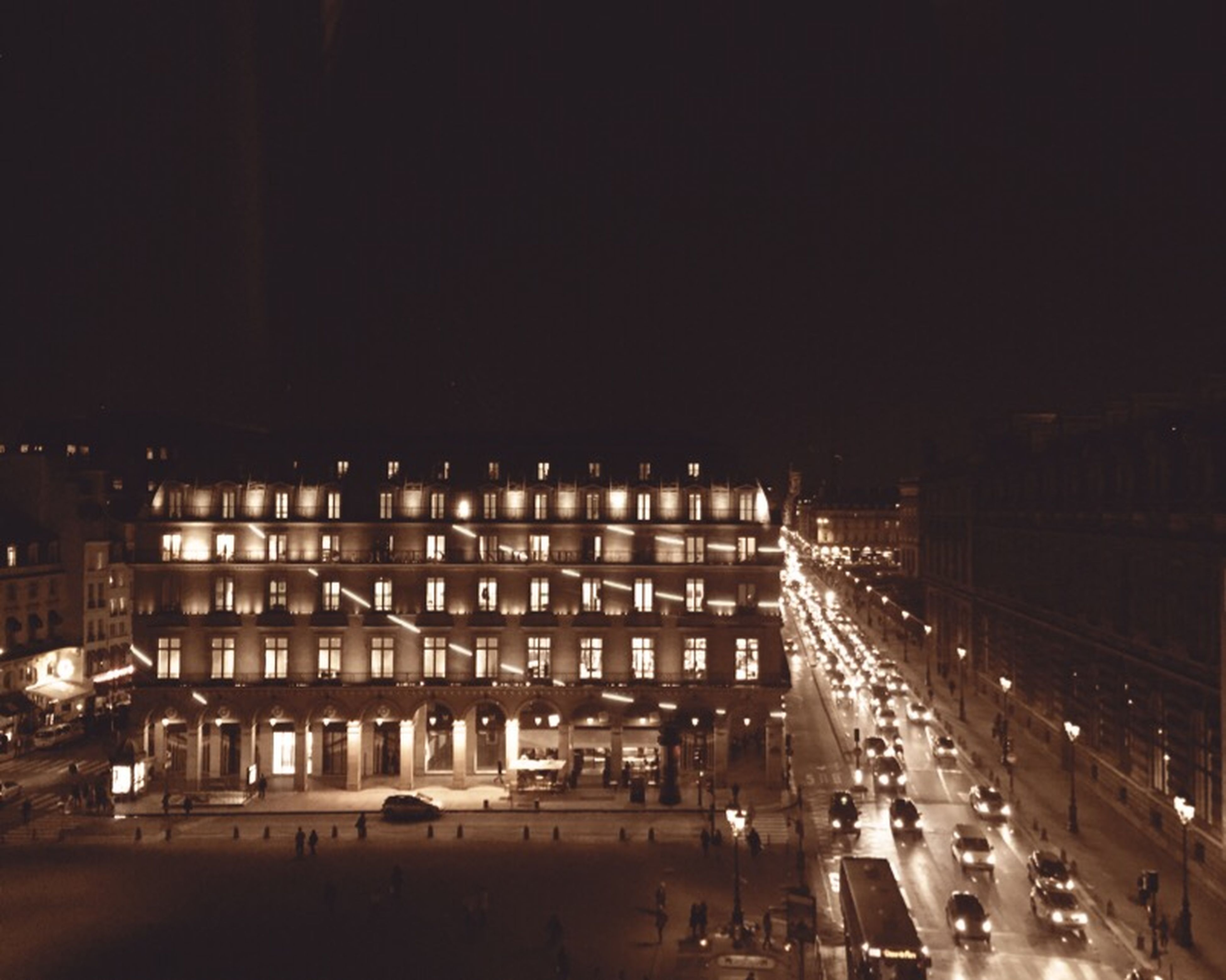 illuminated, night, architecture, built structure, city, building exterior, transportation, city life, street, road, high angle view, clear sky, travel, large group of people, incidental people, railroad station, outdoors, copy space, mode of transport