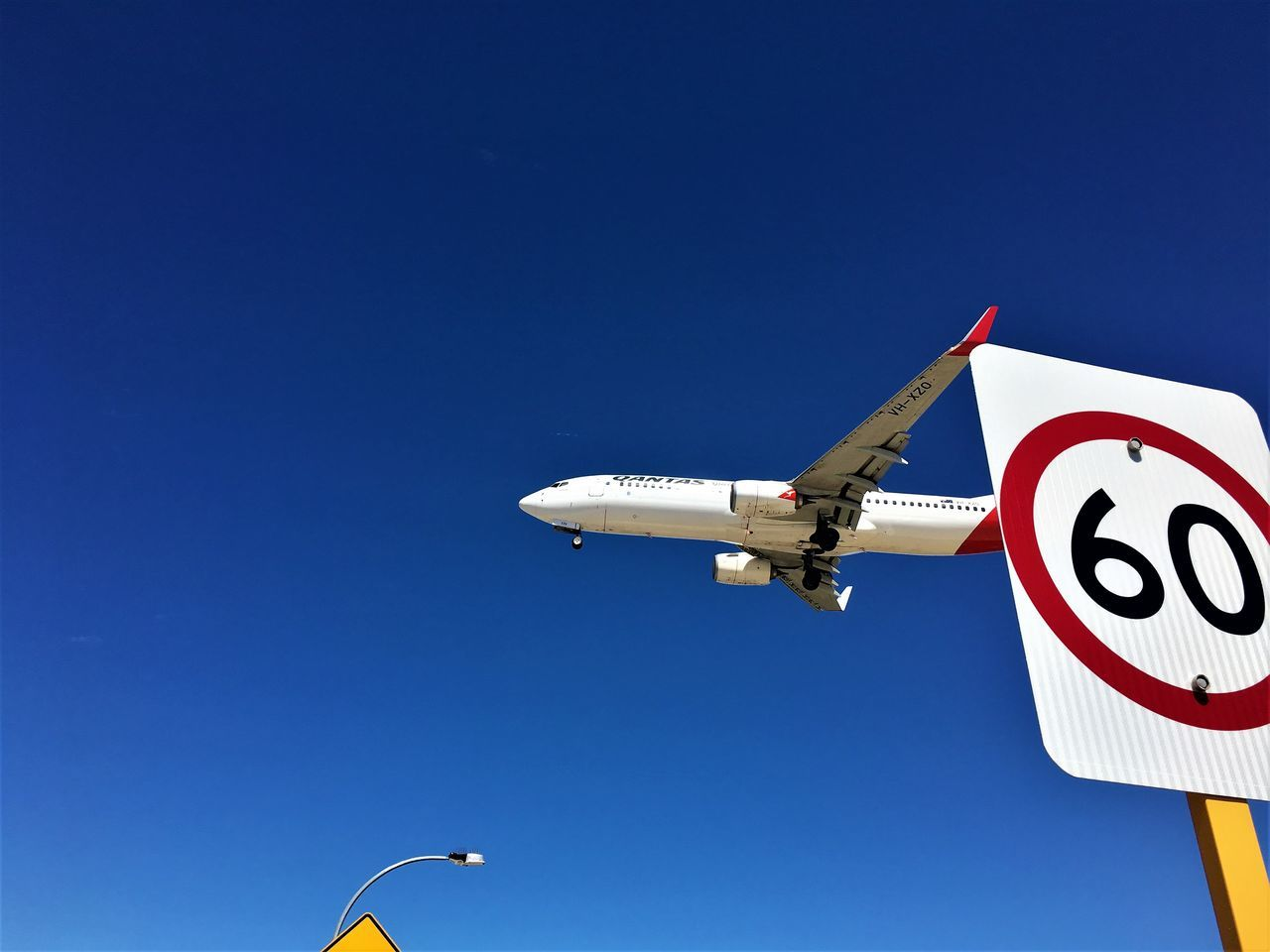 60 Aircraft Airplane Australia Blue Boeing Boeing 737 Clear Sky Day Flying Jet Jet Engine Landing Low Angle View No People Outdoors Plane Qantas Sign Sign Board Signboard Sky Speed Speed Limit Speeding