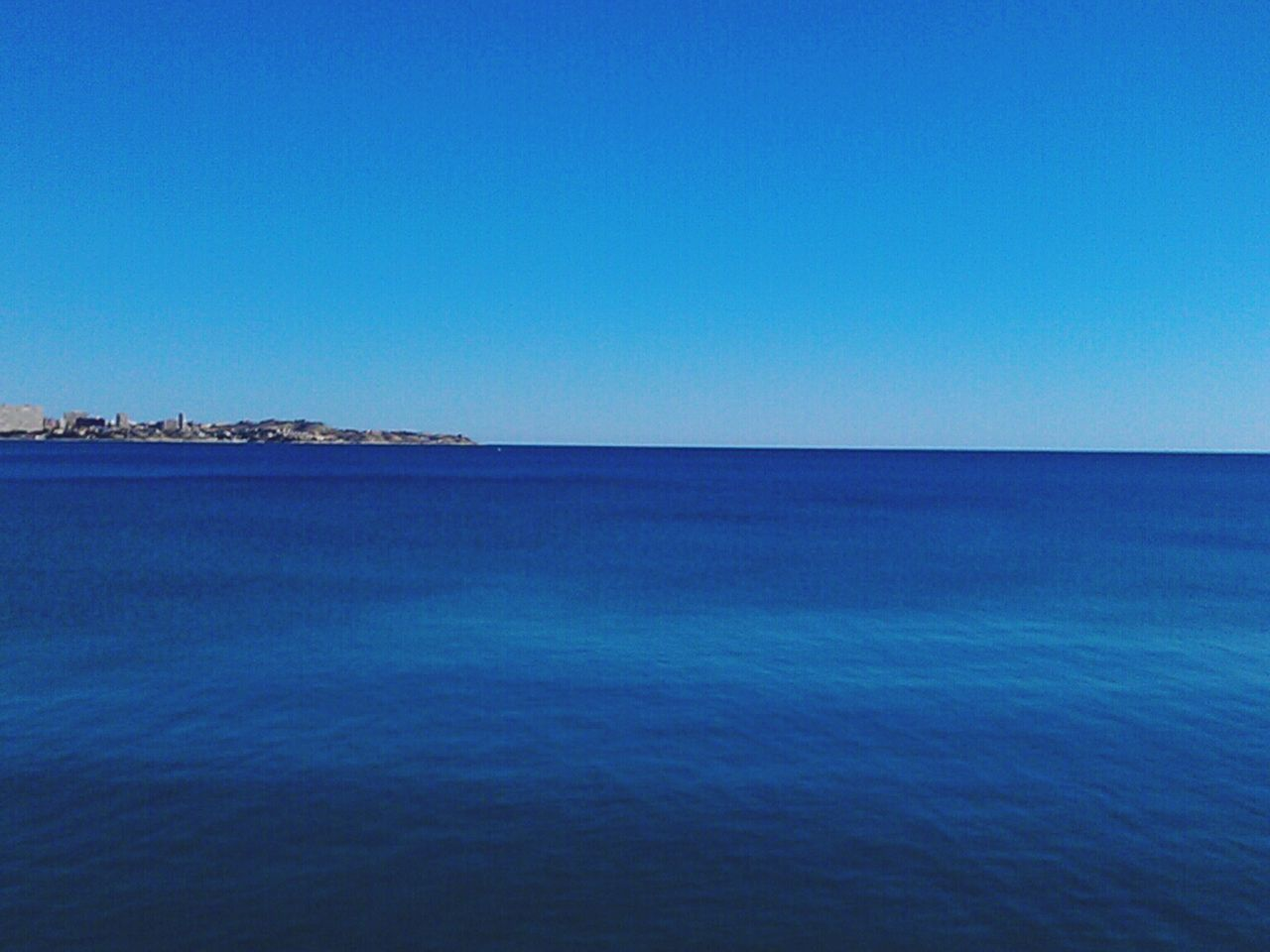 Tranquil View Of Seascape Against Clear Blue Sky