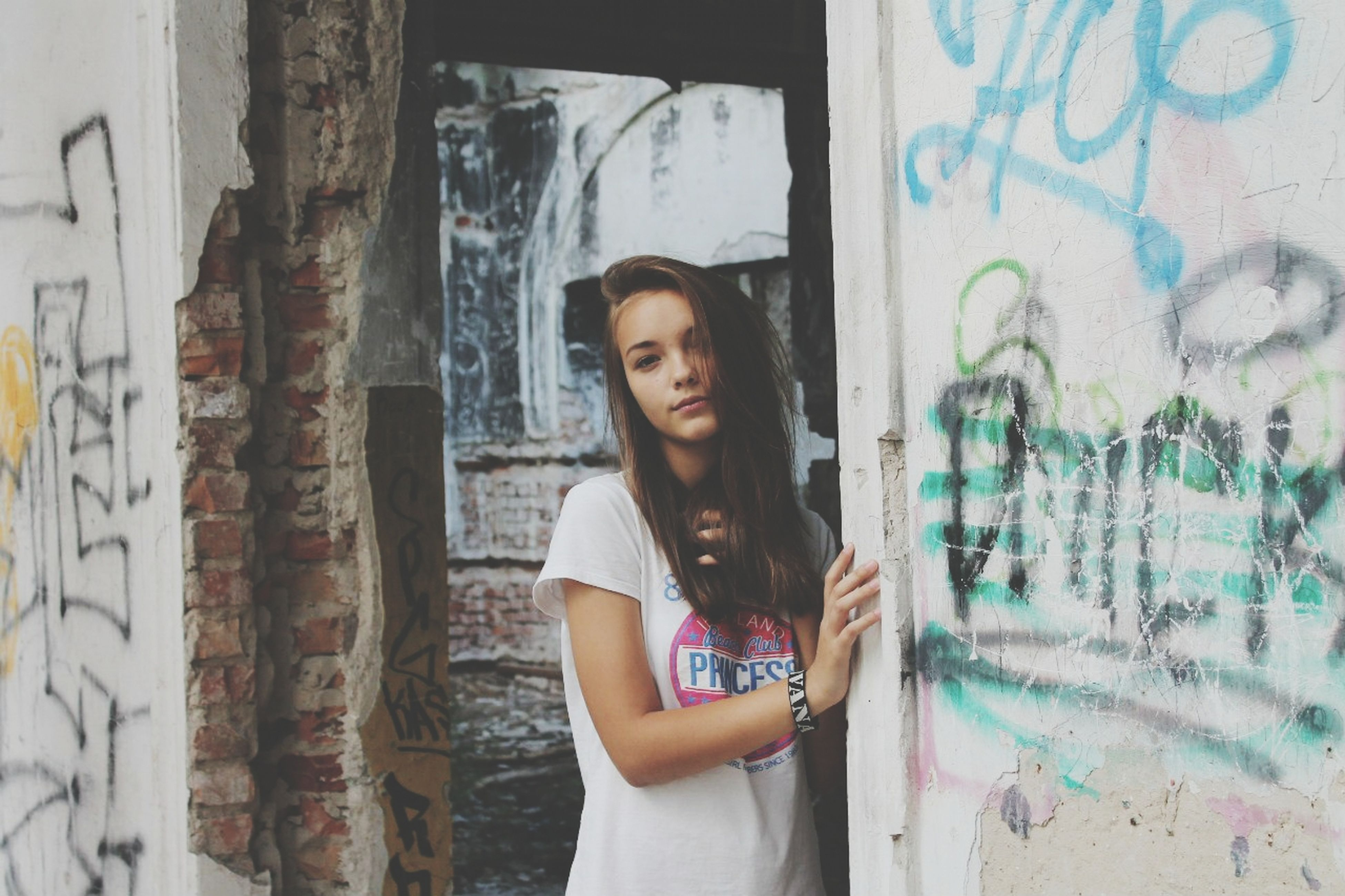 wall - building feature, young adult, graffiti, lifestyles, person, looking at camera, indoors, young women, front view, architecture, casual clothing, portrait, built structure, leisure activity, wall, standing, waist up, art