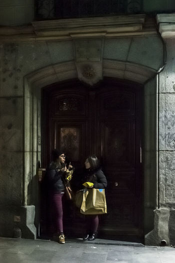 Two young women eating French fries (chips) in a doorway at night. City City Life City Street Dark Eating Shopping Architecture Bag City Lights City View  Corner Doorway Editoral Face Friendship Full Length Night Real People Shadow Street Talking Togetherness Two People Women Young Adult