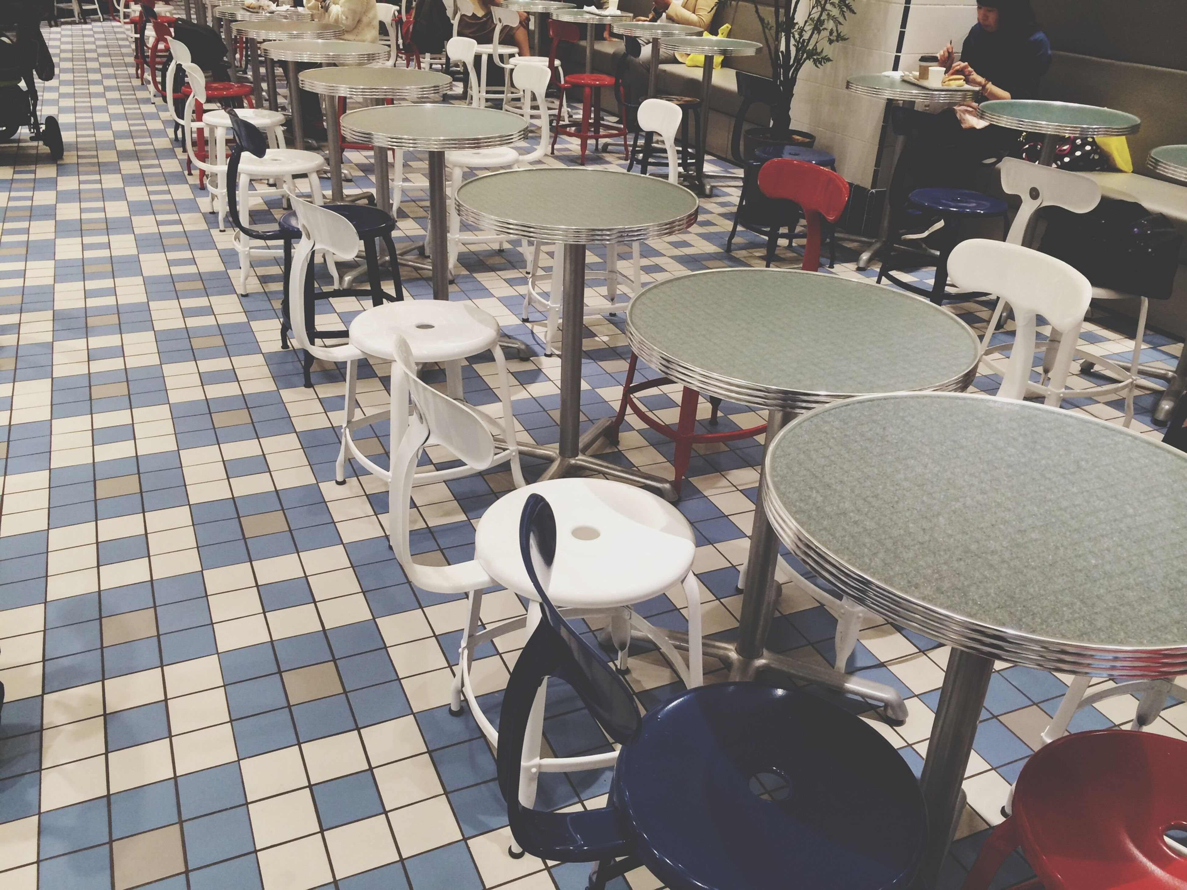 large group of objects, chair, arrangement, abundance, in a row, indoors, hanging, table, lighting equipment, high angle view, variation, restaurant, retail, incidental people, absence, still life, no people, order, choice, day