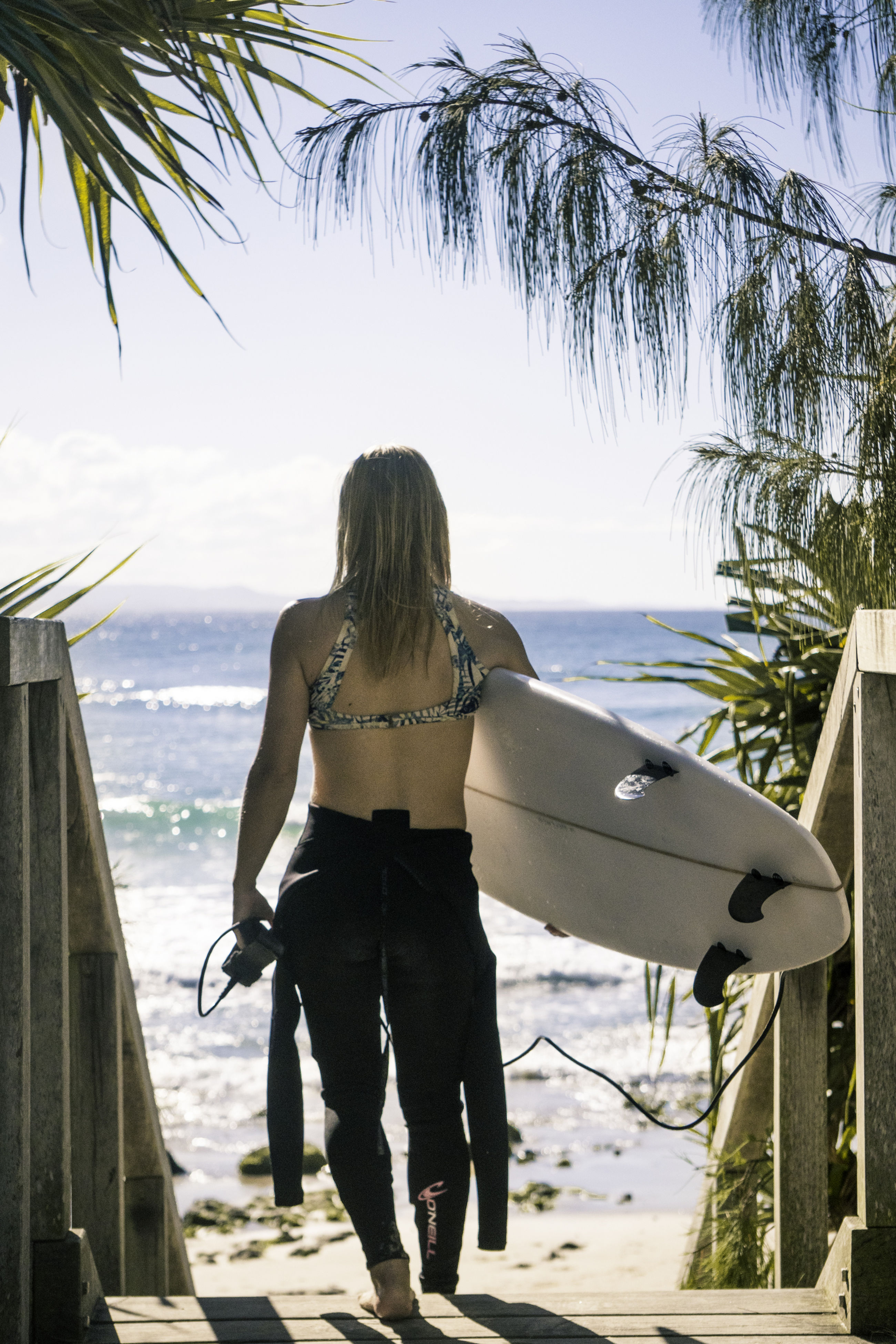 rear view, sea, beach, one person, standing, palm tree, day, outdoors, carrying, leisure activity, horizon over water, real people, nature, vacations, lifestyles, full length, women, sky, tree, nautical vessel, water, young adult, adult, people