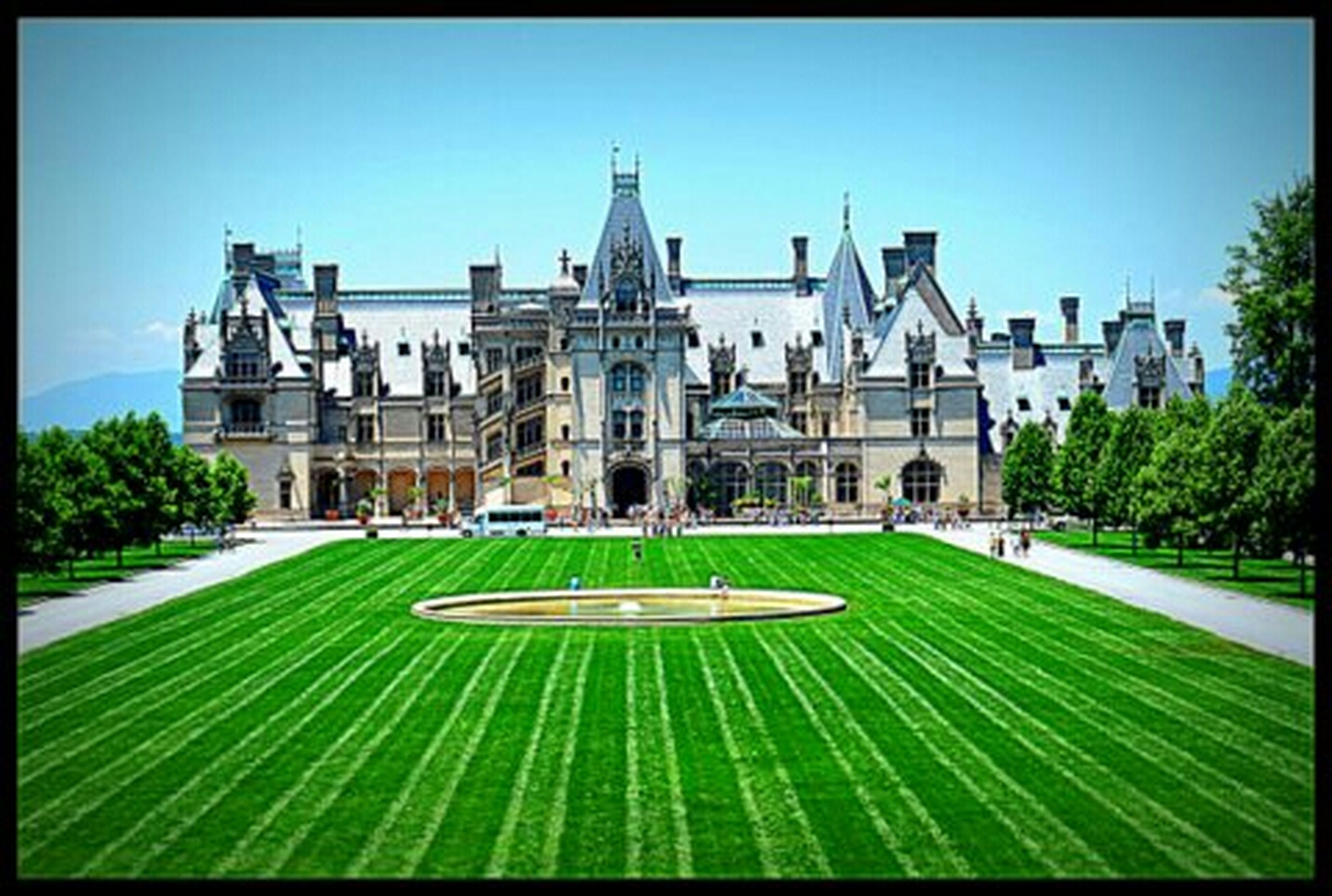architecture, building exterior, built structure, grass, lawn, transfer print, clear sky, green color, famous place, formal garden, tree, travel destinations, auto post production filter, sunlight, facade, city, park - man made space, hedge, history, tourism