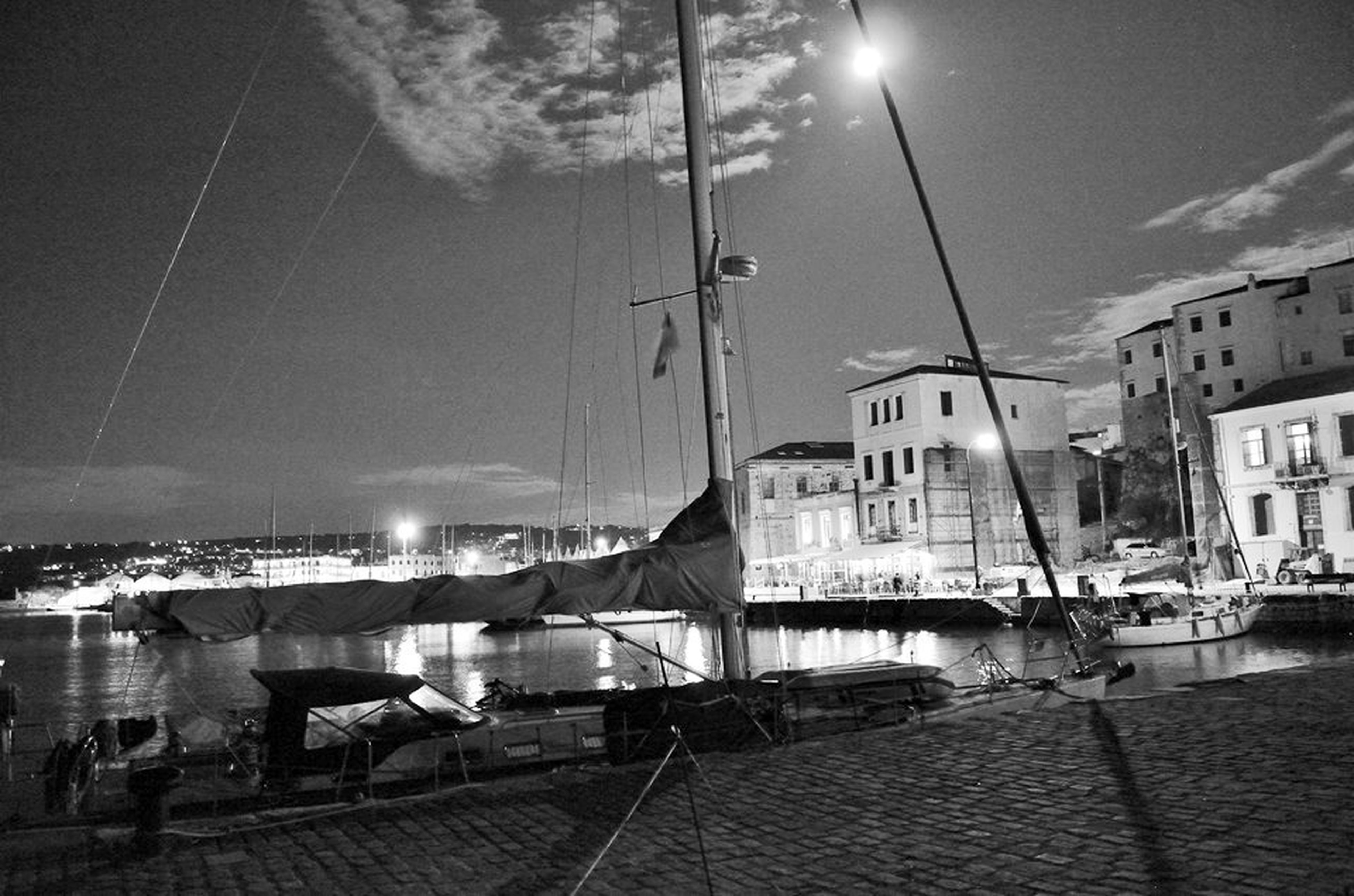 transportation, mode of transport, building exterior, sky, illuminated, nautical vessel, street light, built structure, water, architecture, night, moored, lighting equipment, reflection, boat, the way forward, outdoors, power line, mast, electricity