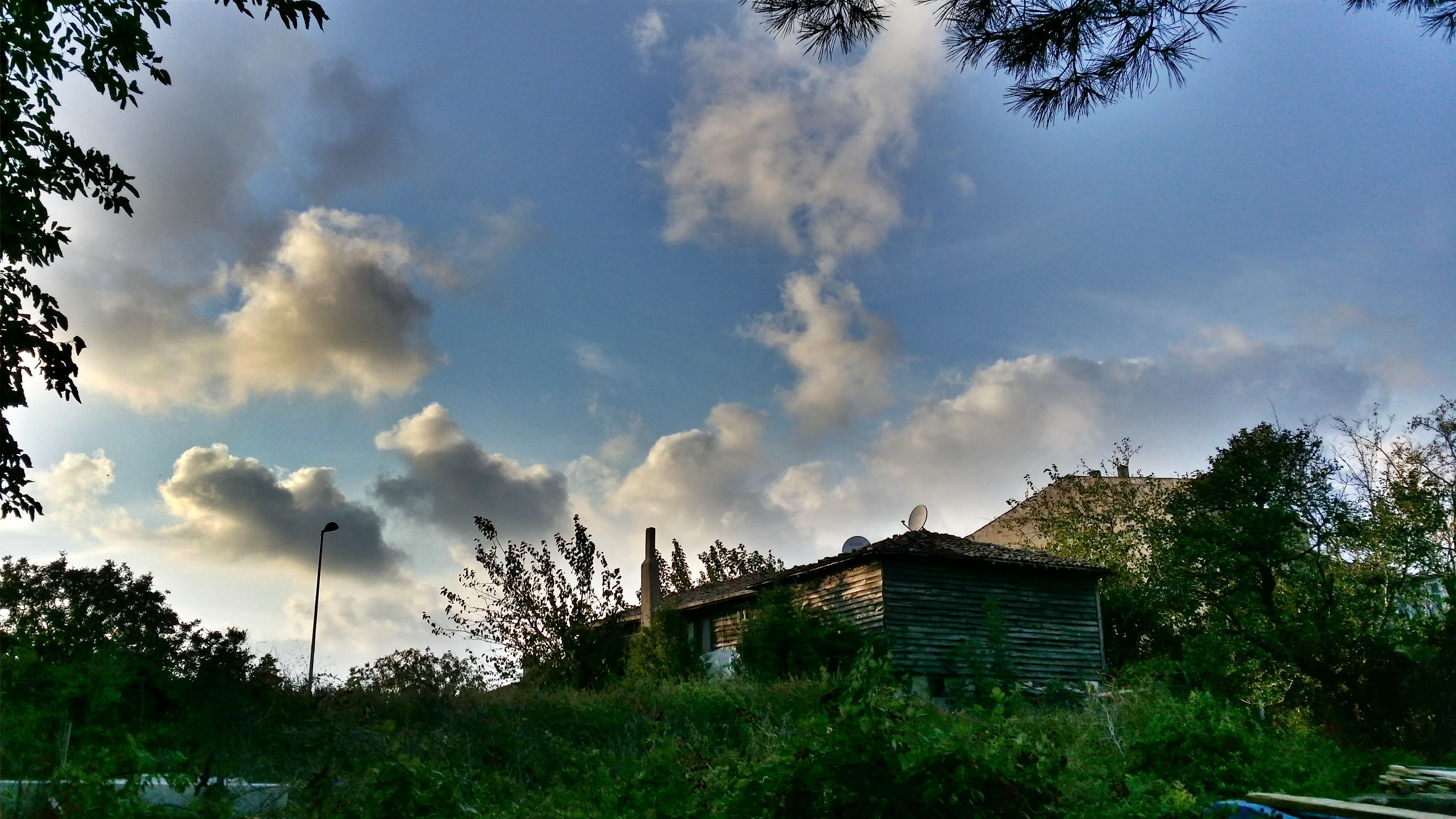 sky, cloud - sky, tree, building exterior, built structure, cloudy, cloud, architecture, house, field, growth, nature, low angle view, grass, tranquility, outdoors, day, tranquil scene, no people, plant