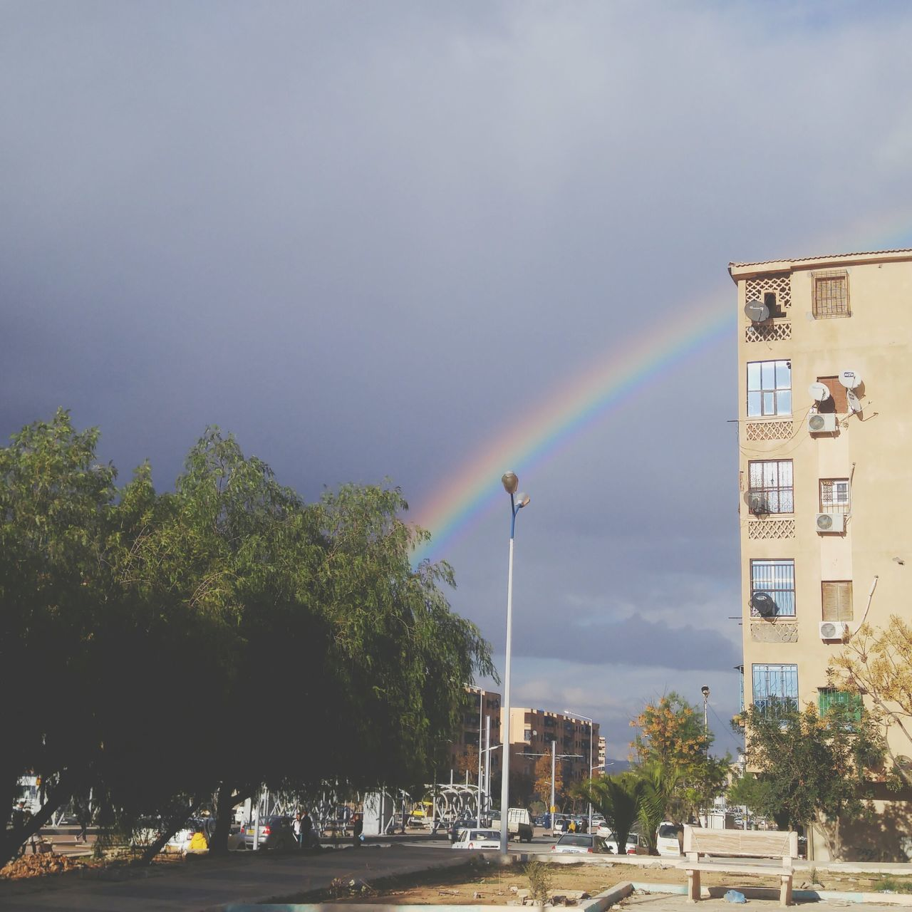 rainbow, tree, building exterior, built structure, architecture, day, car, outdoors, double rainbow, sky, cloud - sky, nature, road, city, no people, beauty in nature