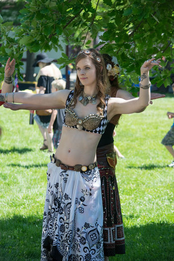 Adult Beautiful Woman Belly Dancer Belly Dancing Celebration Day Front View Grass Holding Leisure Activity Lifestyles One Person Outdoors People Real People Standing Tree Young Adult Young Women