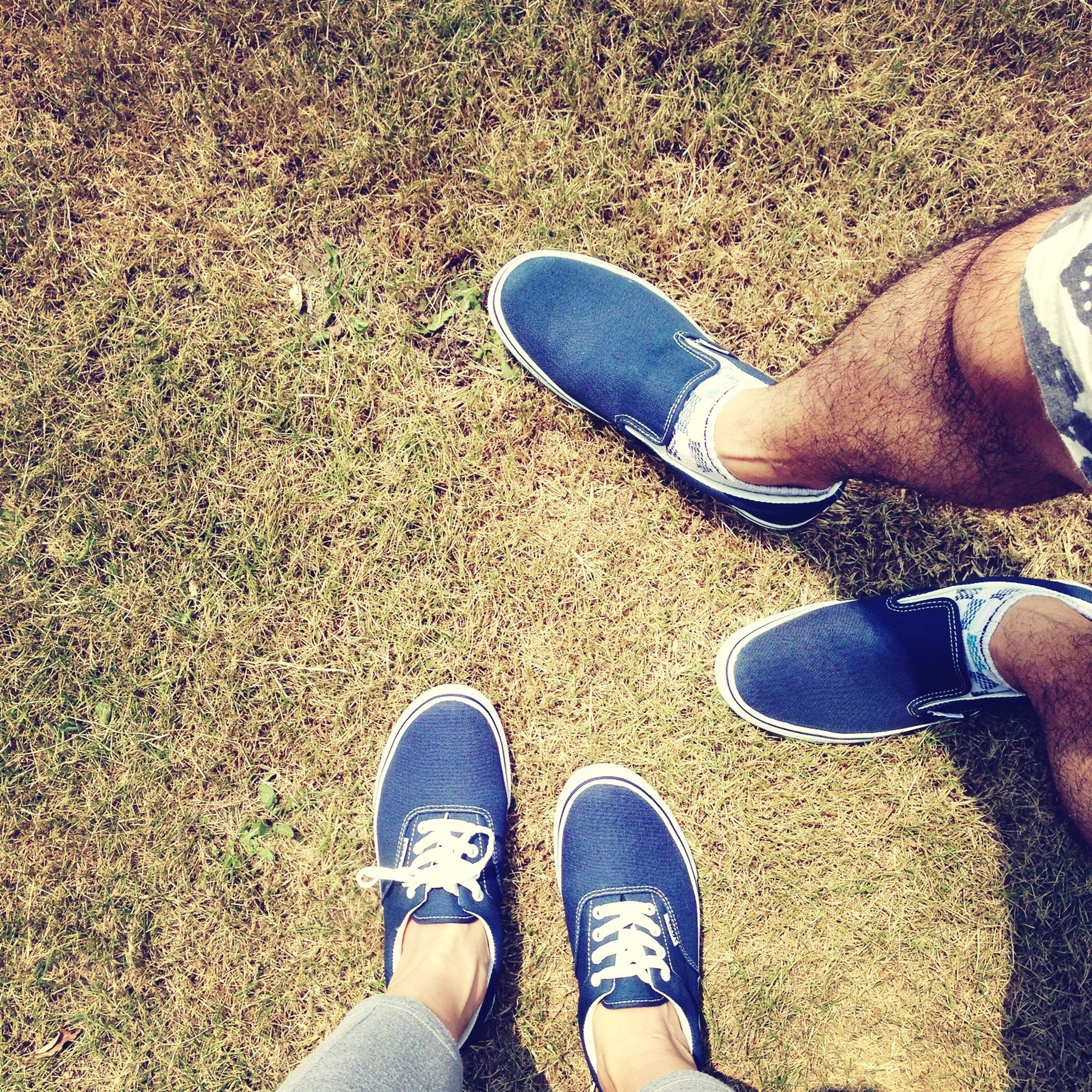 low section, person, shoe, personal perspective, human foot, footwear, standing, high angle view, lifestyles, jeans, leisure activity, canvas shoe, directly above, men, pair, unrecognizable person, outdoors