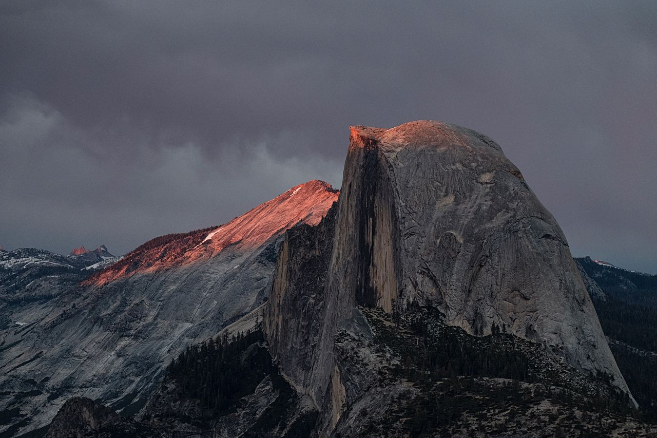 A burst of light pokes through a stormy sky, touching the summit of Half Dome, Cloudrest and the distant Echo Peaks of the Cathedral Range (too small to see on a mobile screen.) It's always worth sticking around -- the light had come and gone in a quick minute. volcano geology lava physical geography active volcano mountain erupting Nature volcanic landscape power in nature Rock formation rock - object sky beauty in Nature outdoors landscape no people volcanic crater Tranquility travel destinations