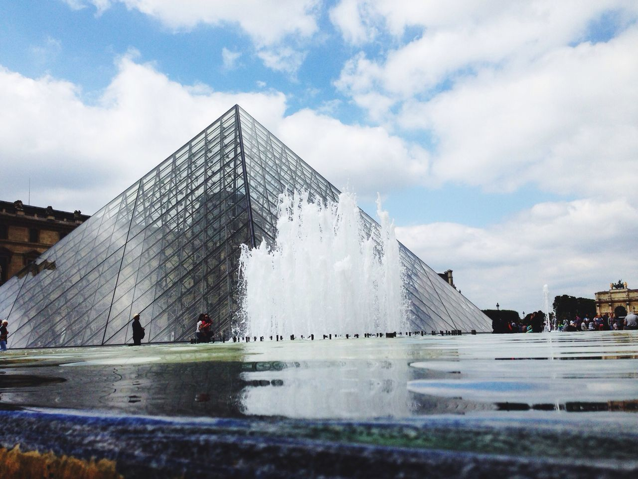 Fountain In Front Of Built Structure Against Clouds