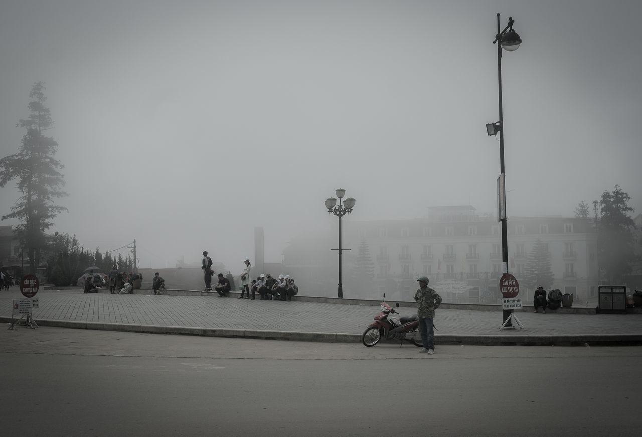 People On Sidewalk In Foggy Weather Against Sky