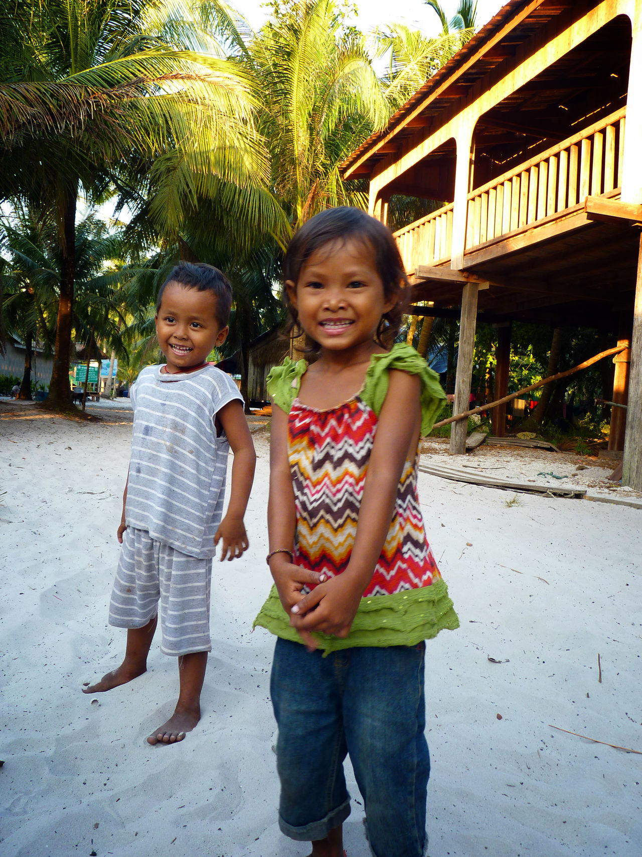 ASIA Asian Children Cambodia Childhood Composition Front View Happiness Innocence Lifestyles Looking At Camera Palm Trees Person Perspective Portrait Real People Sand Smiling Togetherness Travel Travel Photography Traveling Wooden House