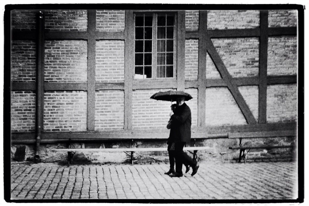 Man And Woman Sharing Umbrella Walking On Footpath