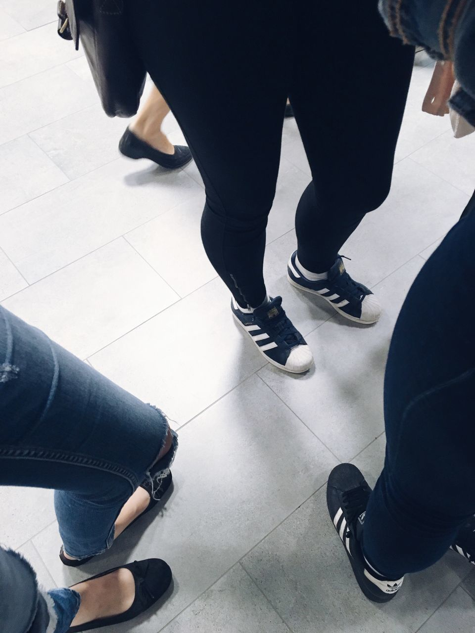 low section, high angle view, human leg, indoors, shoe, real people, standing, women, men, two people, technology, day, adult, people