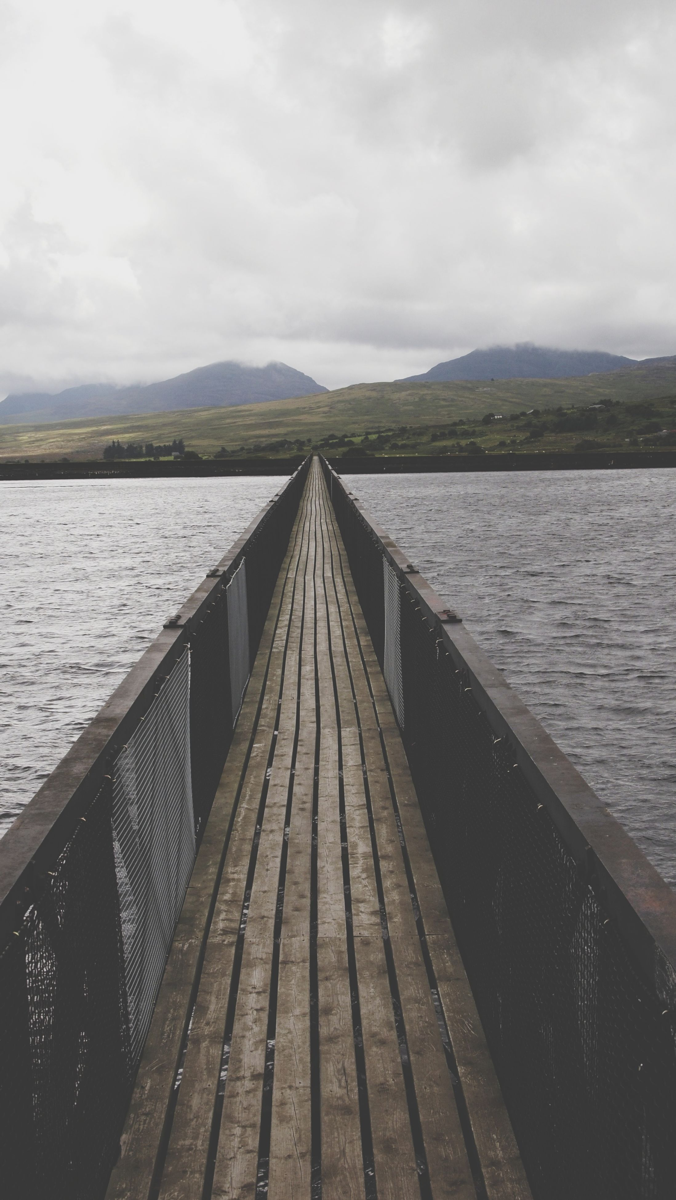 water, sky, the way forward, pier, cloud - sky, built structure, tranquil scene, tranquility, cloud, cloudy, sea, diminishing perspective, lake, architecture, jetty, scenics, wood - material, mountain, nature, railing