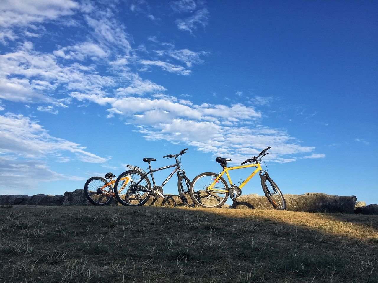 bicycle, field, sky, transportation, blue, grass, mode of transport, land vehicle, nature, stationary, landscape, cloud - sky, tranquil scene, outdoors, day, tranquility, beauty in nature, scenics, rural scene, mountain bike, no people