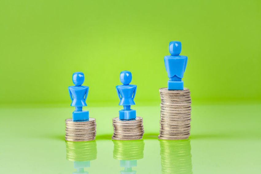 Male and female figurines standing on top of columns of coins. Wage gap concept illustration. Balance Bar Graph Blue Business Business Business Finance And Industry Choice Close-up Coins Colored Background Copy Space Day Female Figurines  Gender Equality Green Background Green Color Large Group Of Objects Male No People Pile Of Coins Stack Studio Shot Wage Gap