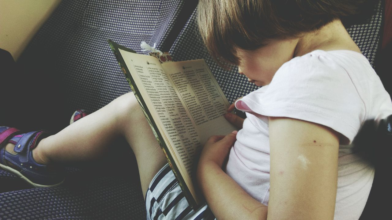 High Angle View Of Girl Reading Book In Car