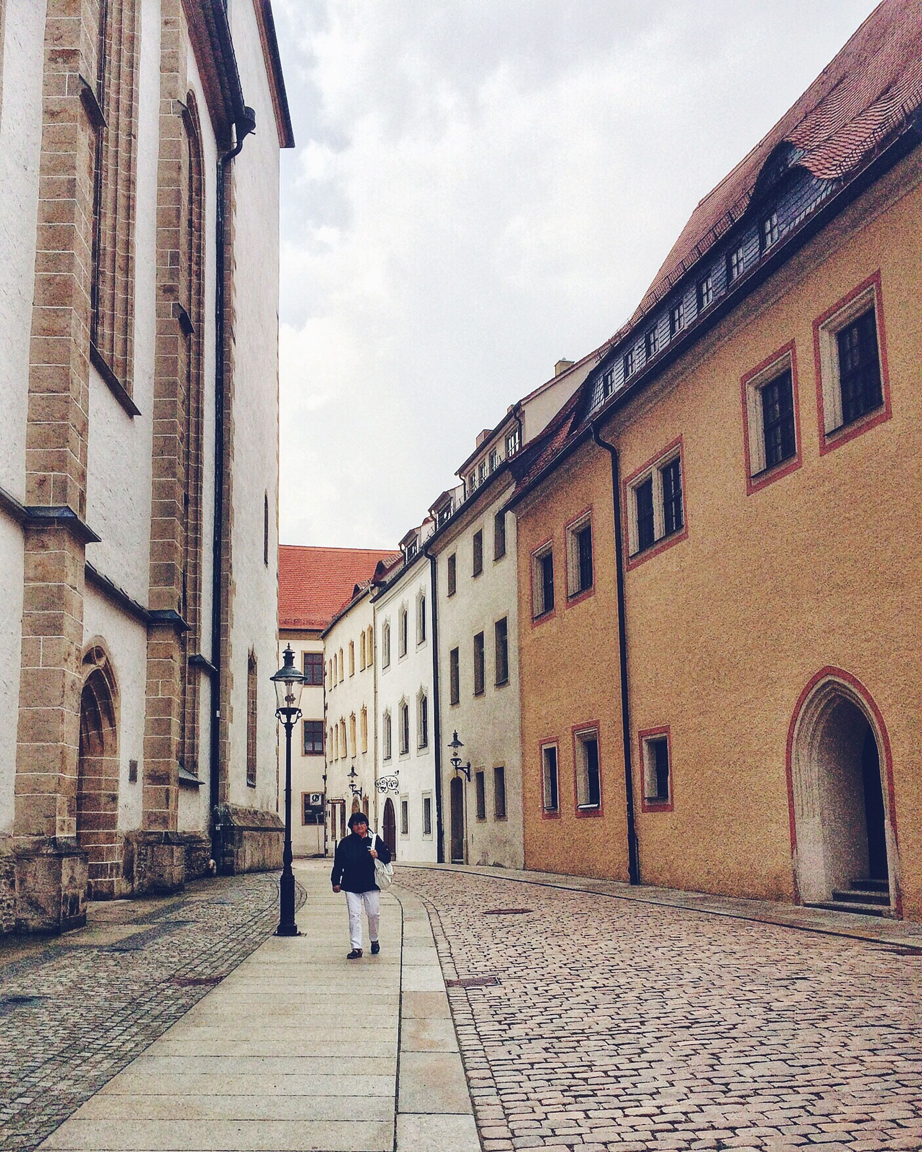 building exterior, architecture, built structure, cobblestone, sky, walking, men, lifestyles, person, the way forward, full length, street, leisure activity, city, building, rear view, residential building, cloud - sky
