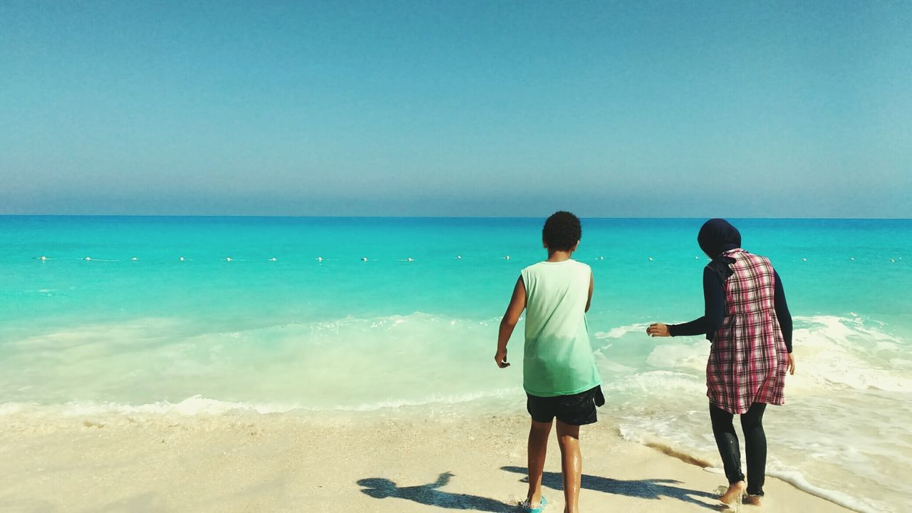 sea, horizon over water, rear view, beach, two people, real people, water, shore, scenics, clear sky, sky, nature, standing, men, sand, full length, sunlight, beauty in nature, leisure activity, blue, day, shadow, togetherness, lifestyles, vacations, outdoors, wave, adult, people