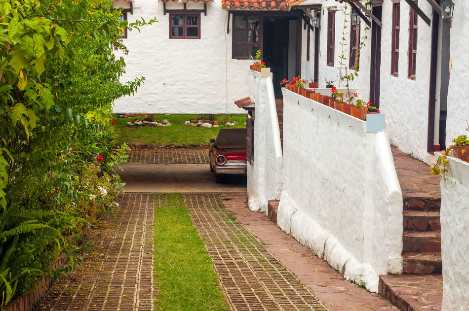 Old red classic car next to white colonial style houses Architecture Building Colombia Colonial Different Exterior Green Historic Home House Latin Old Outdoors Residence Size Stone Style Town Travel Typical Villa De Leyva  Wall Window Windows Wood