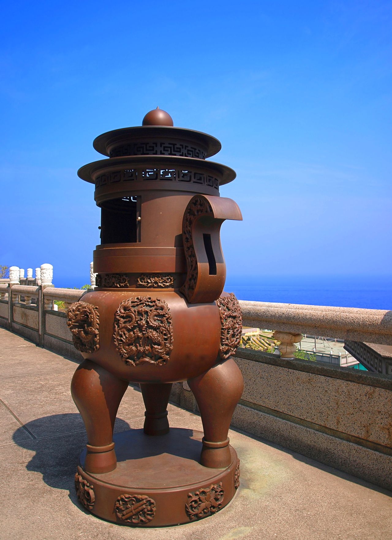 A massive bronze incense burner on a terrace outside a Chinese temple Bronze Sculpture Bronze Vessel Buddhist Temple Cauldron Incense Burner Ocean View Sky Summer Taiwan Temple Terrace