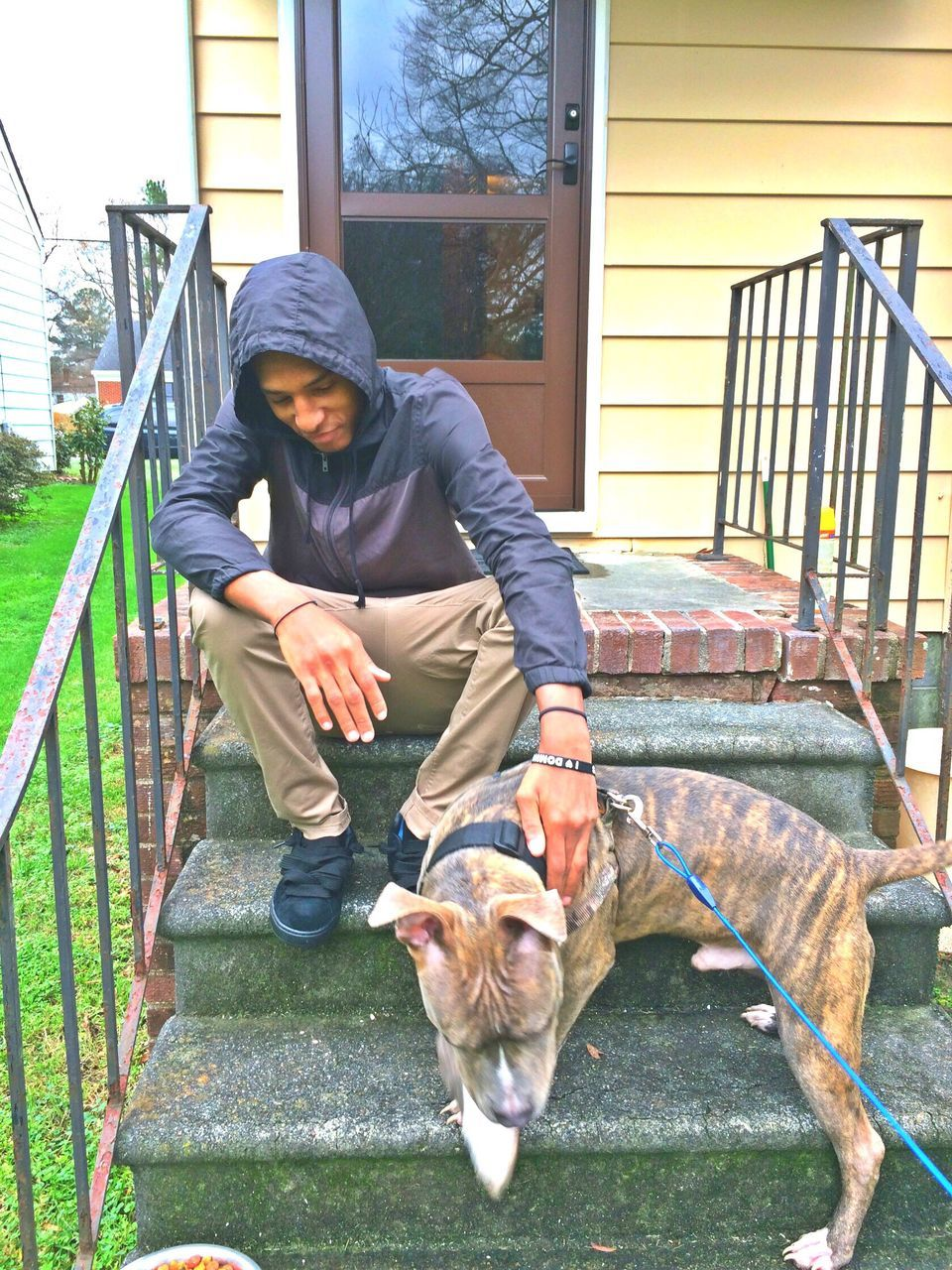 Man Sitting With Dog On Front Stoop