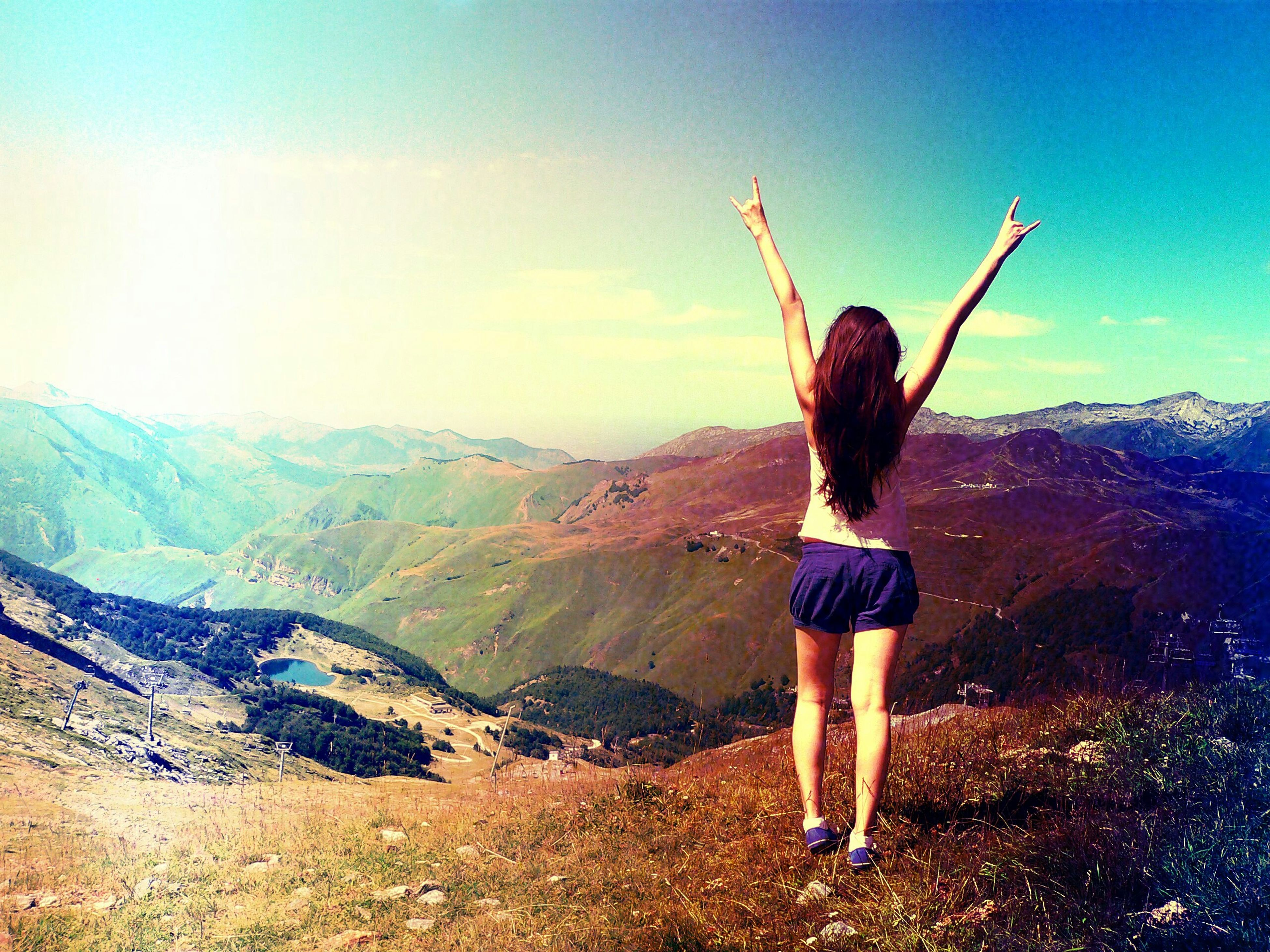 full length, lifestyles, leisure activity, mountain, standing, casual clothing, sky, tranquil scene, landscape, tranquility, scenics, young adult, beauty in nature, nature, rear view, arms outstretched, young women, mountain range