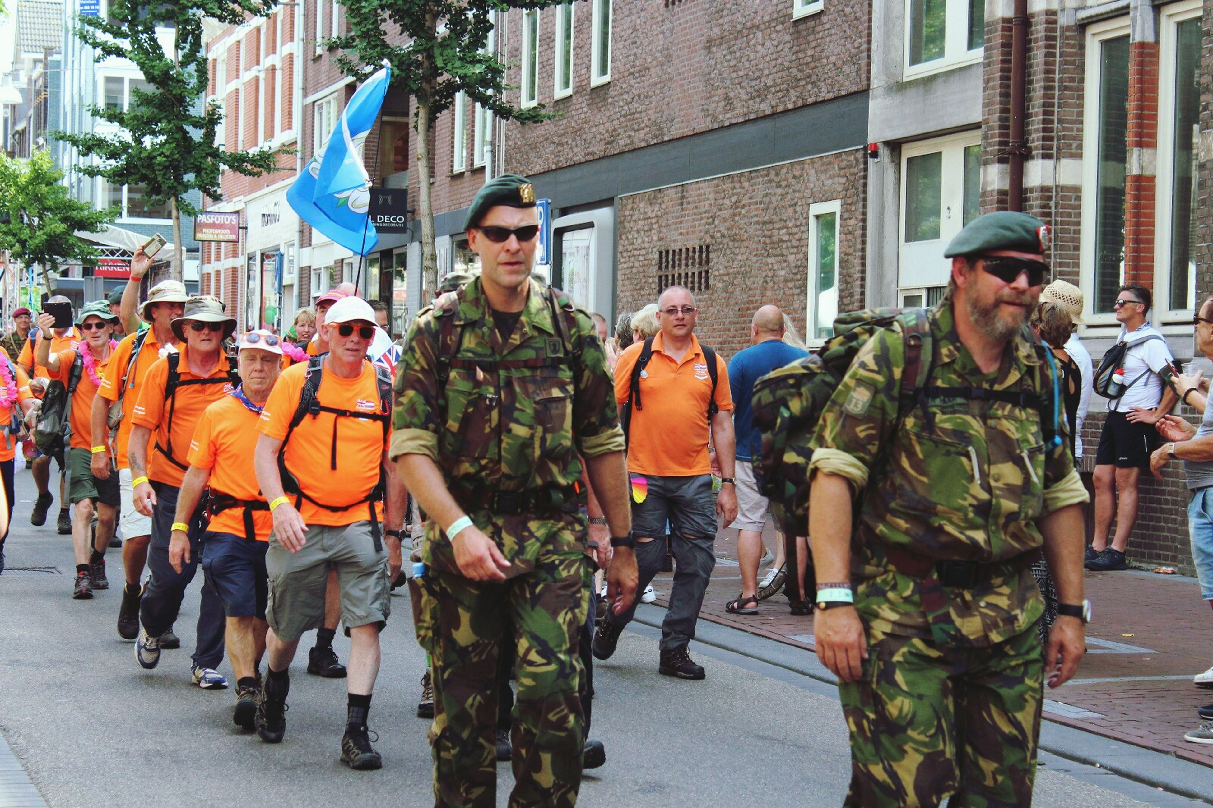 mid adult, mid adult men, building exterior, men, medium group of people, city, street, adult, women, mature adult, day, architecture, standing, built structure, group of people, full length, outdoors, uniform, police force, people, real people, togetherness, adults only, reflective clothing, young adult, only men, camouflage clothing