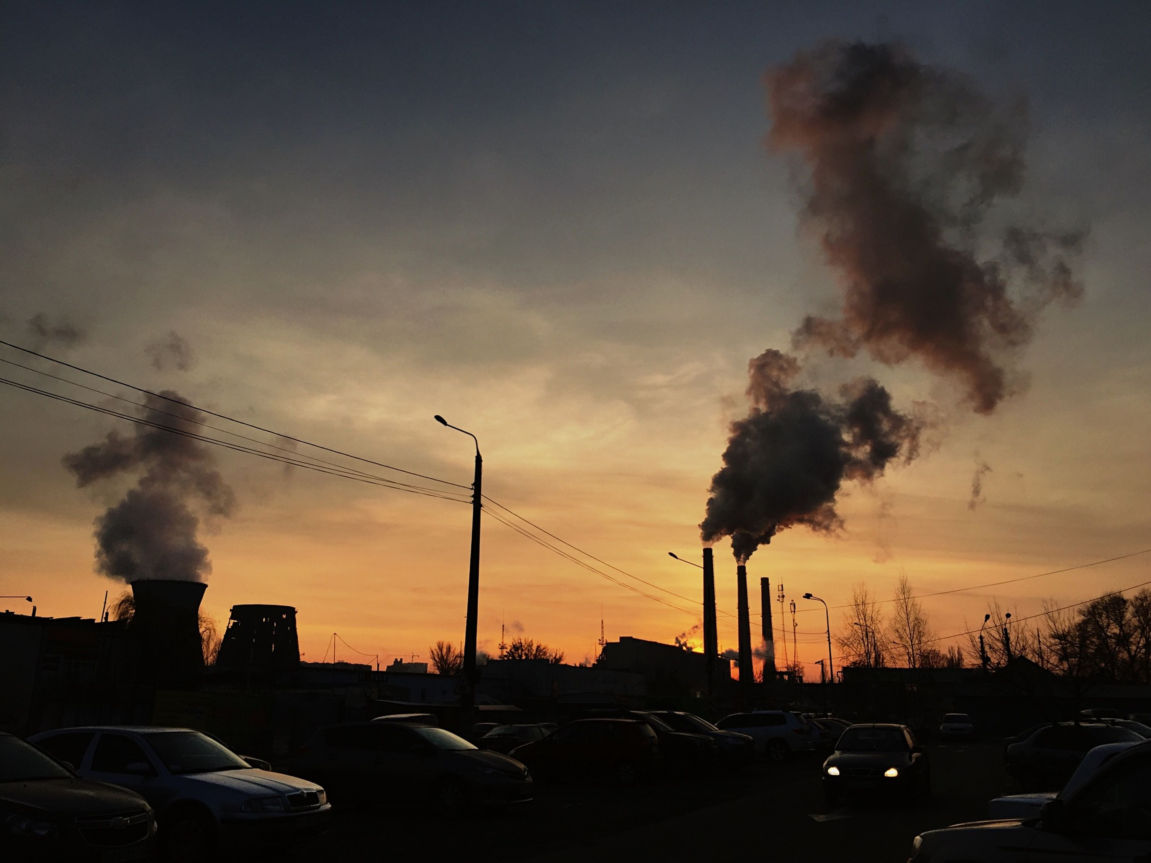 built structure, car, pollution, sky, sunset, architecture, cloud - sky, building exterior, smoke - physical structure, smoke stack, emitting, land vehicle, transportation, no people, city, silhouette, factory, industry, outdoors, fumes, chimney, tall, road, tree, electricity pylon, nature, day