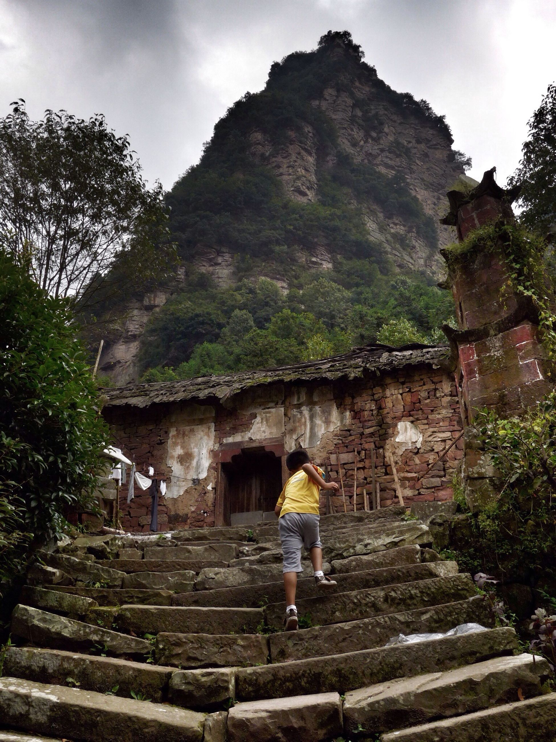 lifestyles, built structure, leisure activity, sky, men, architecture, tree, full length, old, person, abandoned, rear view, mountain, building exterior, steps, rock - object, old ruin, obsolete
