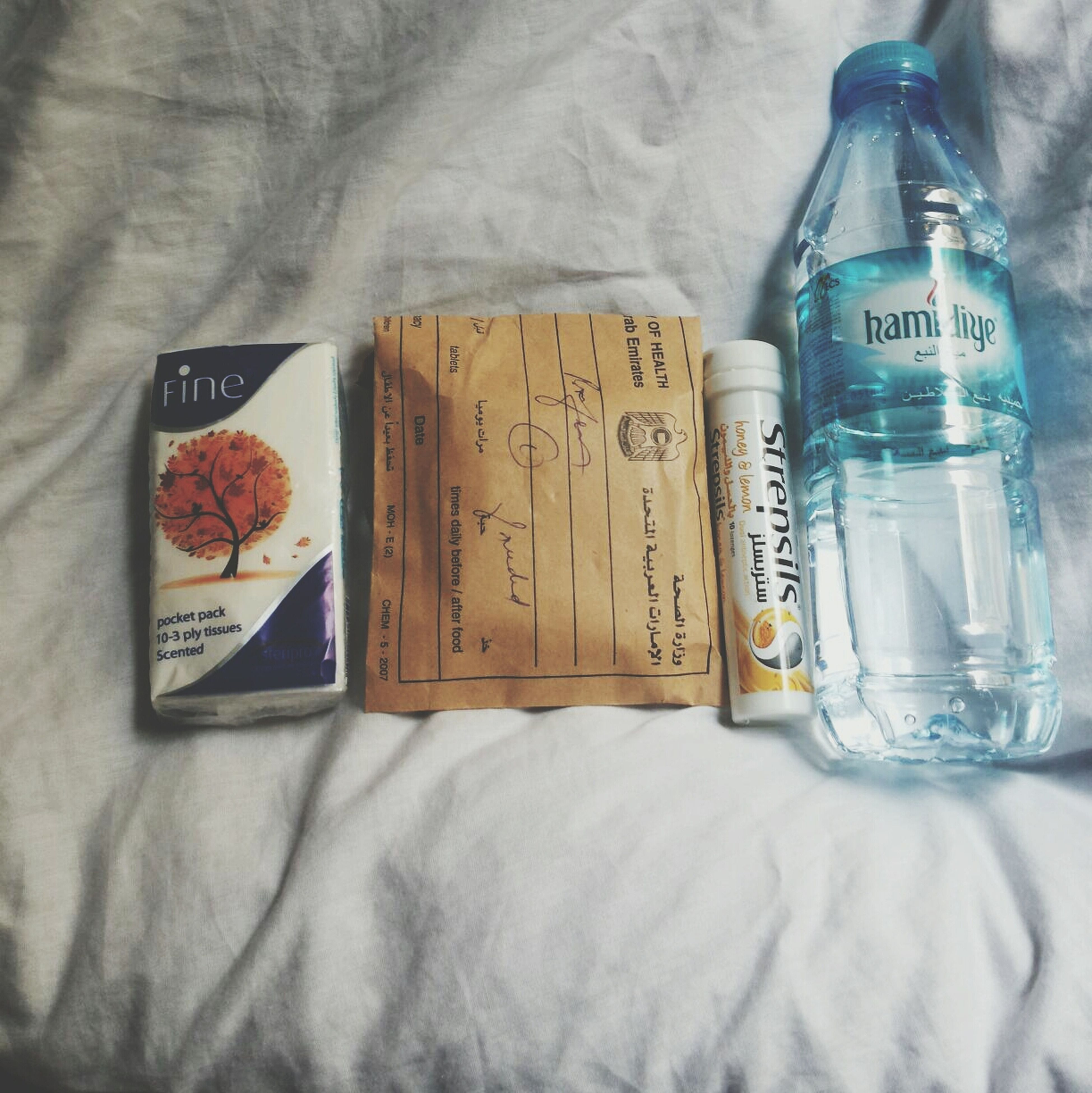 indoors, text, still life, western script, table, close-up, communication, glass - material, drink, paper, food and drink, book, bottle, transparent, drinking glass, no people, refreshment, variation, jar, high angle view