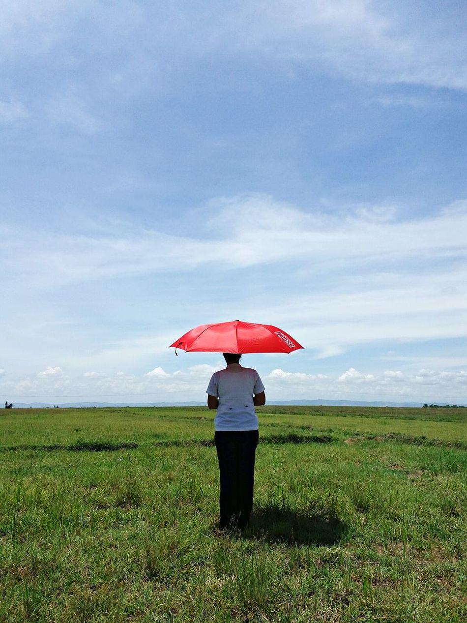 Tranquility.. Umbrella Standing Rear View Field Red Landscape Tranquility Sky Growth Tranquil Scene Scenics Nature Day Plant Cloud - Sky Sunny Student Nurse Community EyeEm Eyeem Philippines Eyeem Nature EyeEm Best Shots Filipino Nature Green Color